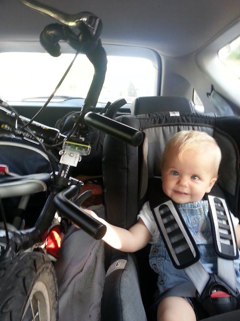 Little girl sat by a racing bike in a car