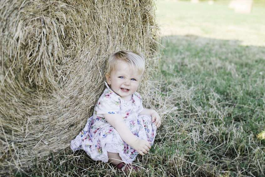 Nelsons Teetha baby teething guide baby sat by hay bale