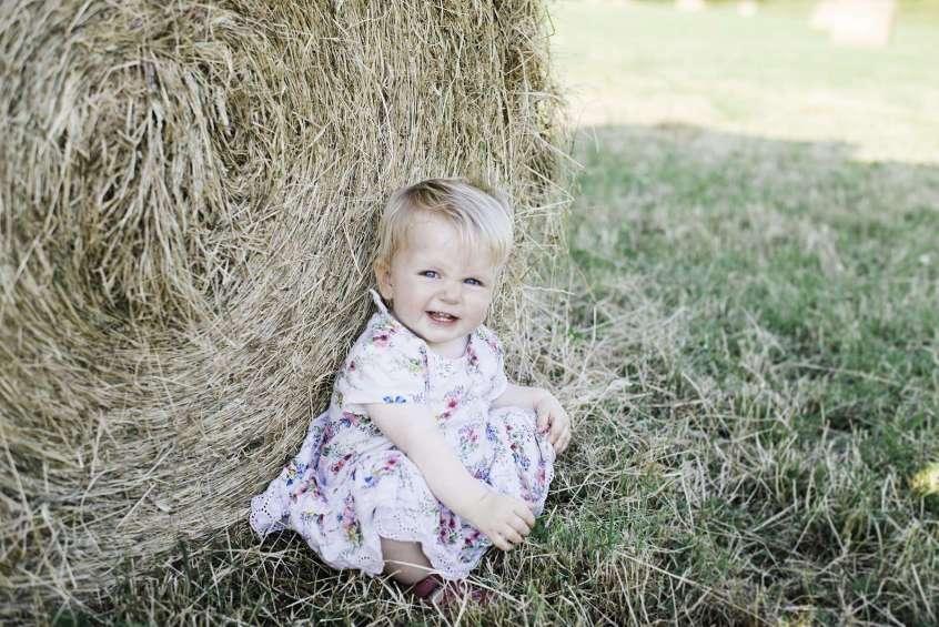 Nelsons Teetha baby teething guide baby sat by hay bale