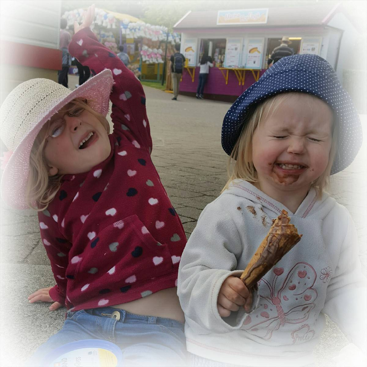two little girls in sun hats and jumpers, one with her arm in the air smiling, the other holding an ice cream with chocolate ice cream all round her face.