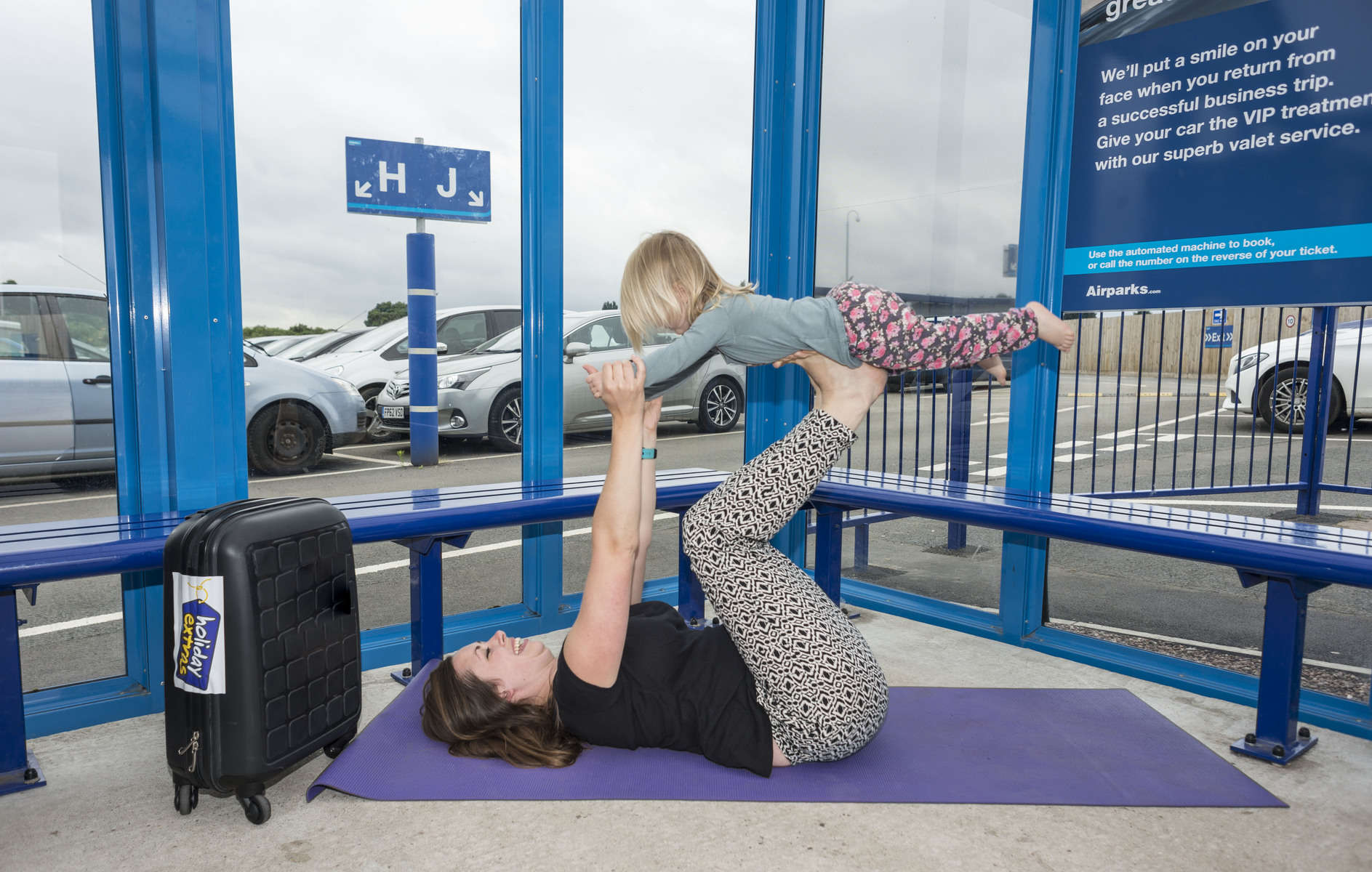 Mum and young daughter doing a yoga pose with child on mum's feet