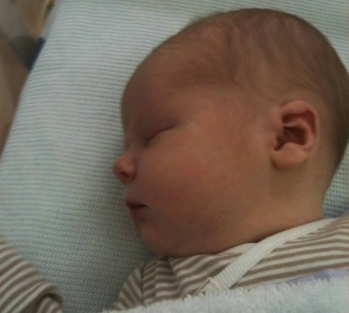 A baby asleep in a crib wearing a brown and white striped top