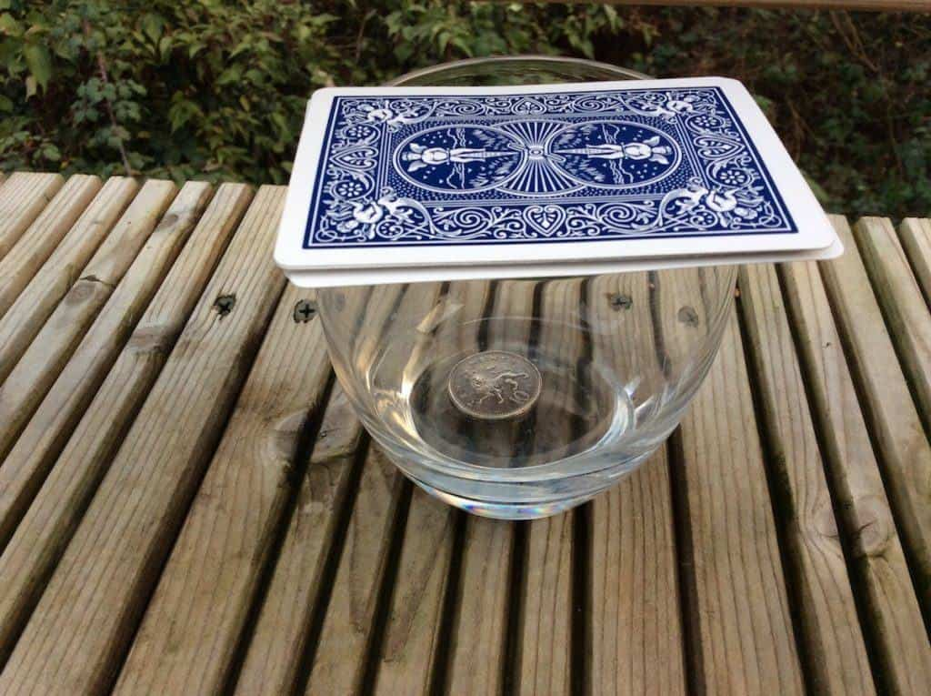 Abracademy card and coin magic trick - cards on top of a glass containing a 10p coin