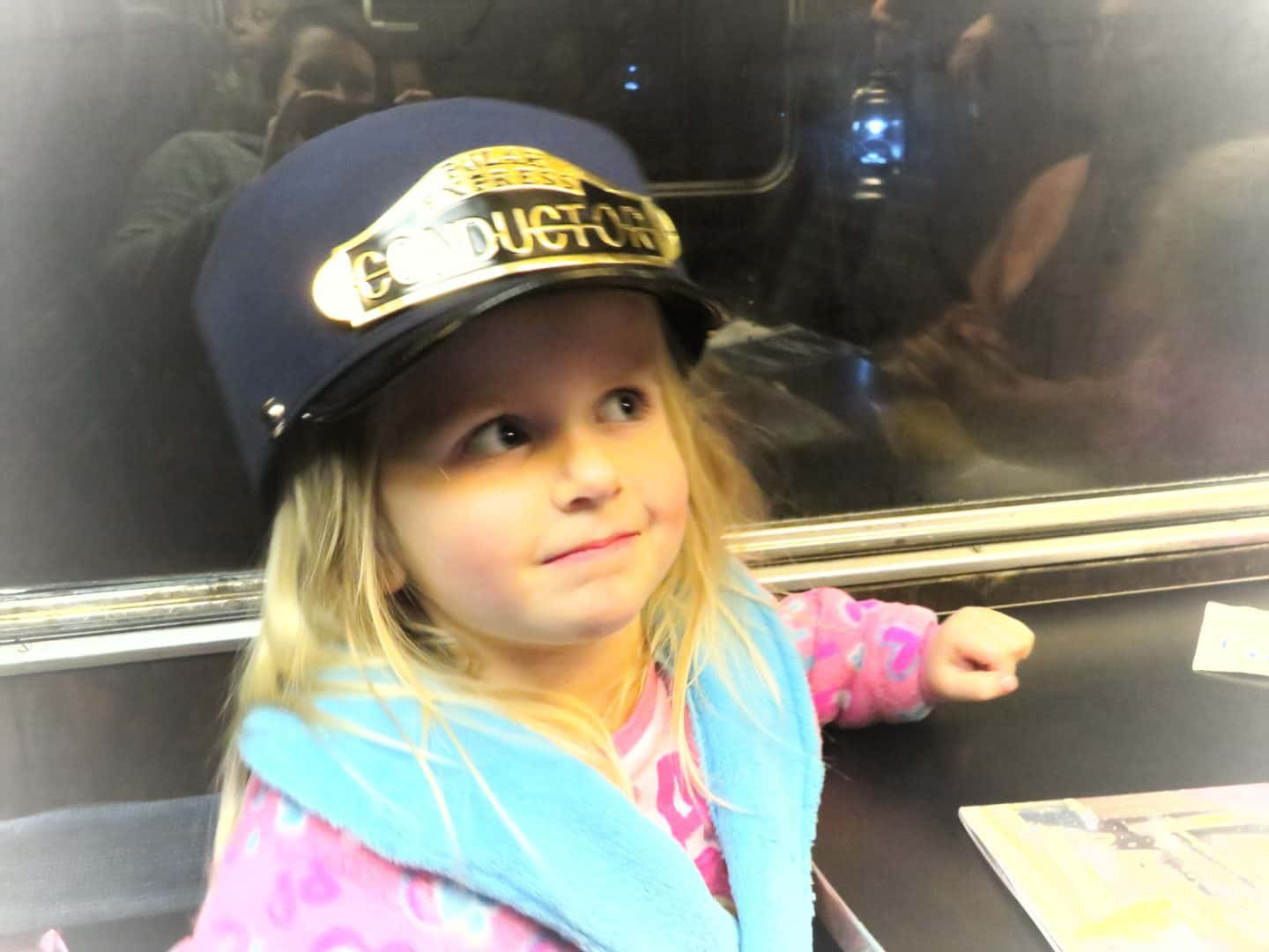 Little girl in a dressing gown wearing the polar express conductor's hat