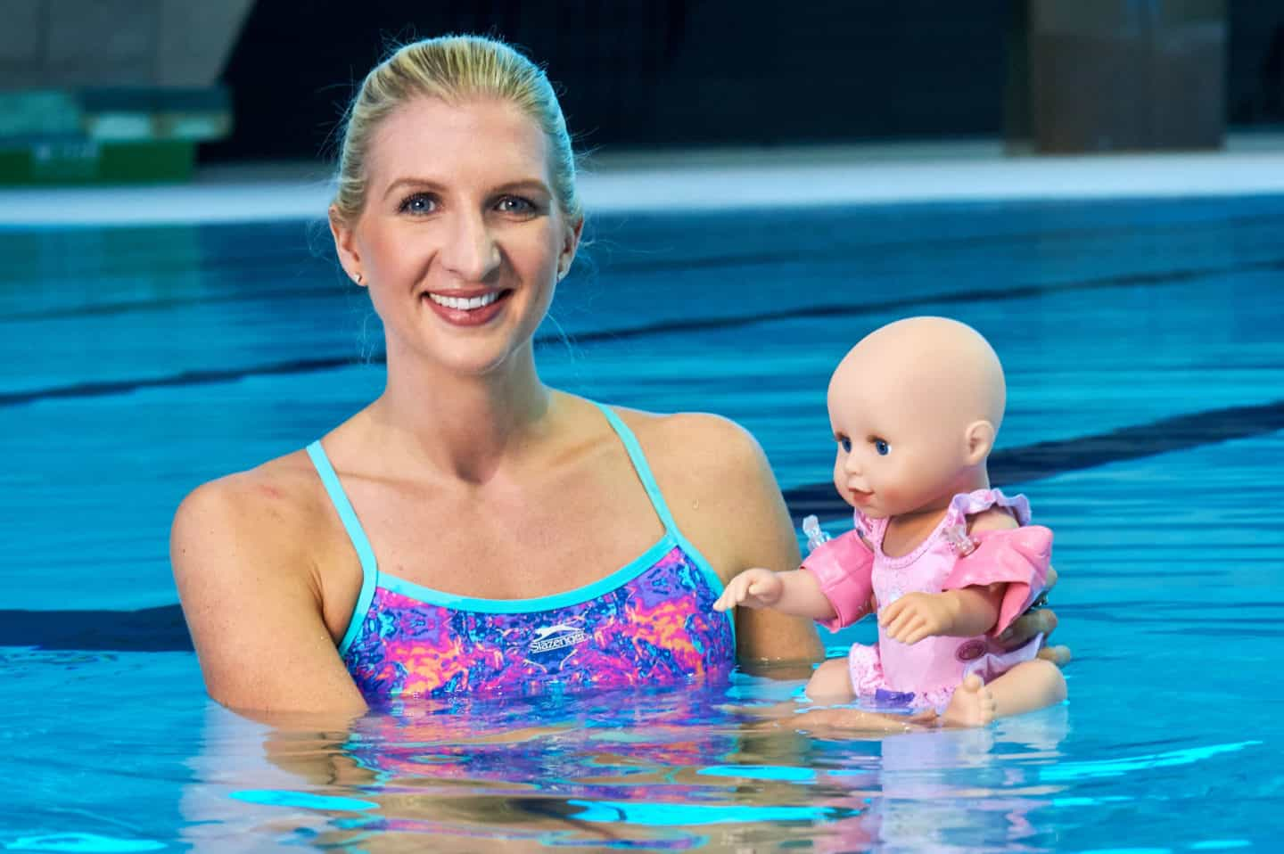 Rebecca Adlington standing in a swimming pool holding a children's doll