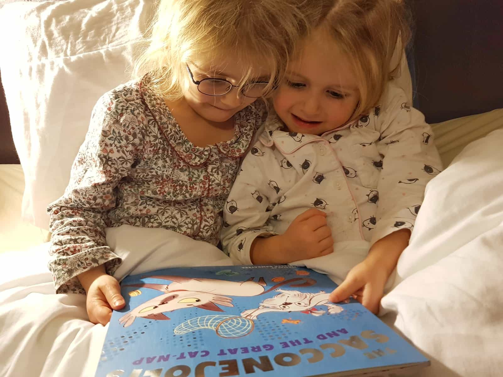 Two little girls looking at the cover of the Great Cat Nap
