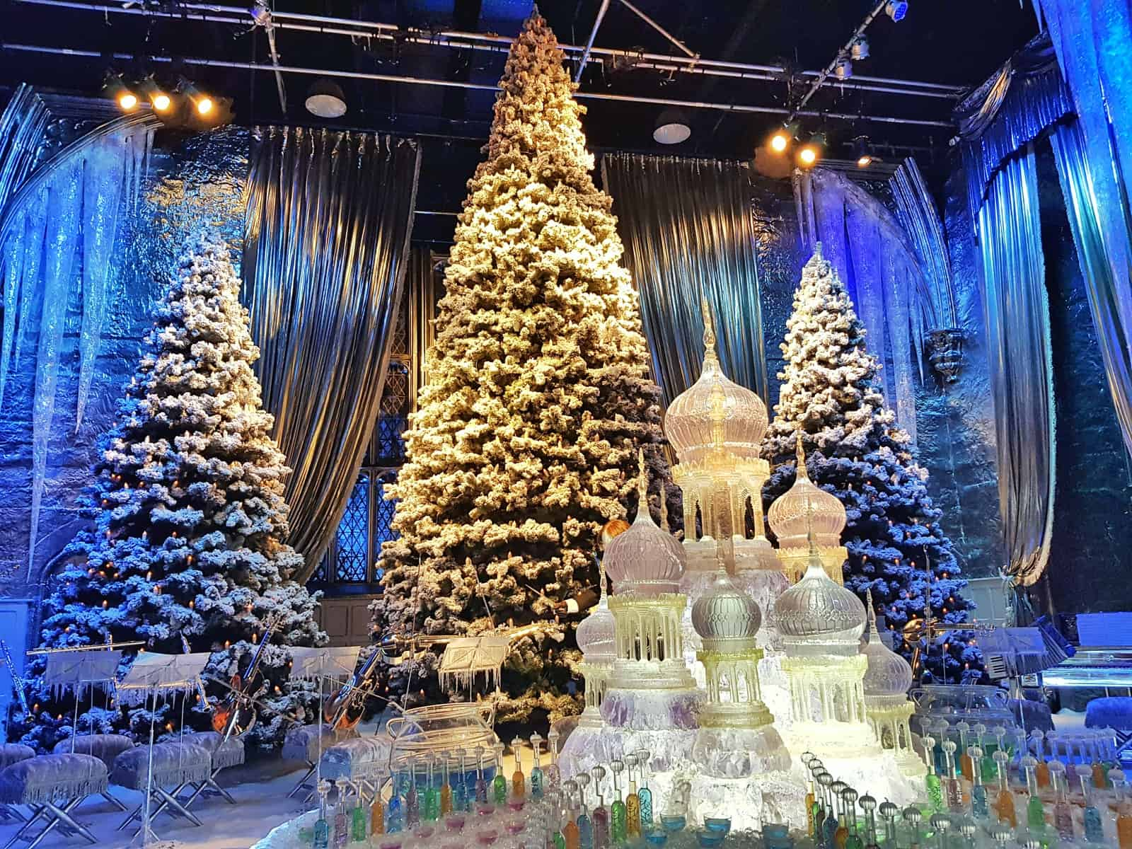 Christmas trees behind ornate ice sculpture