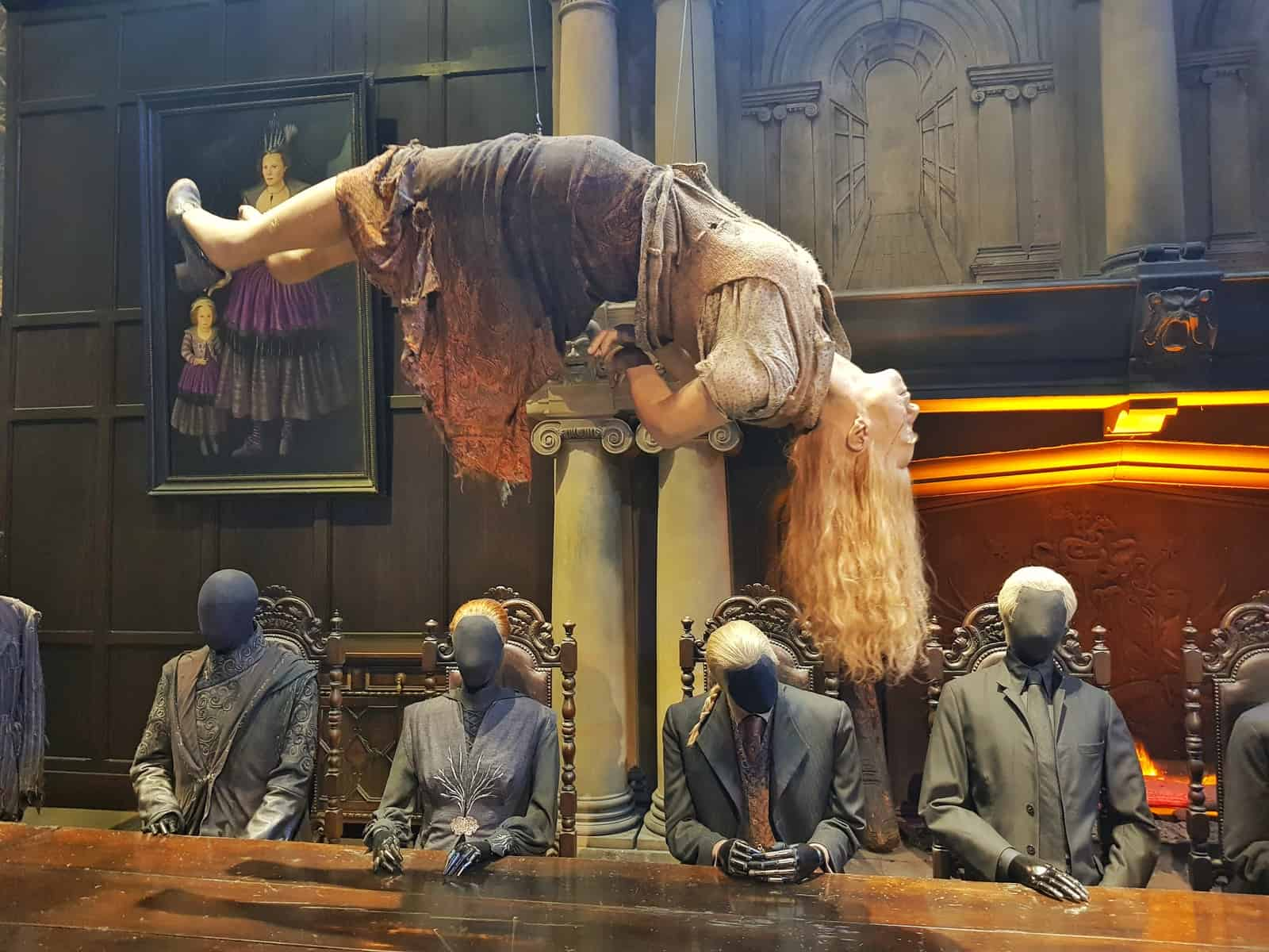 dementors sat around a large table with a girl suspended above them lying down
