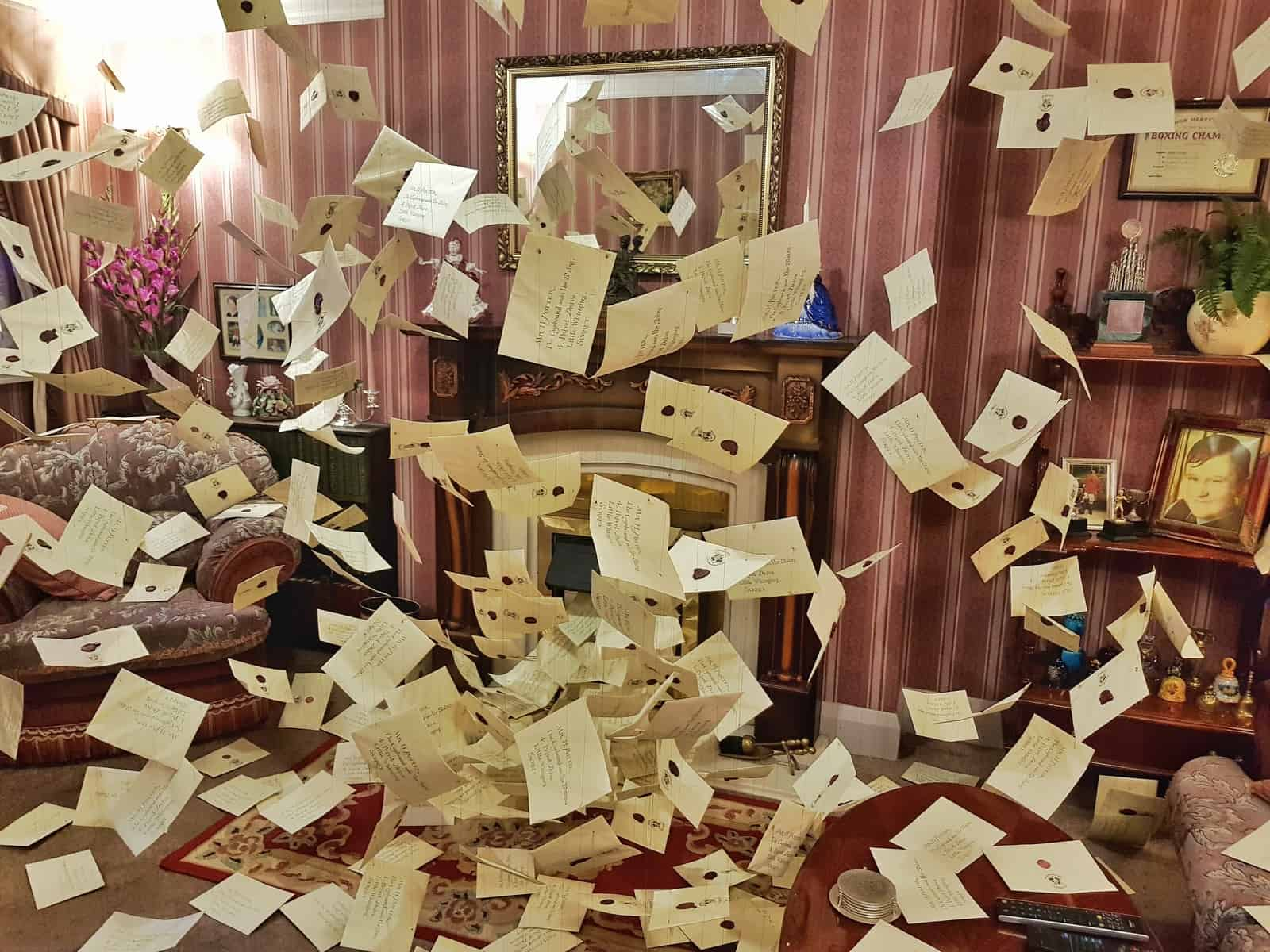 The inside of the living room at 1 Privet drive with letters swirling around in the air
