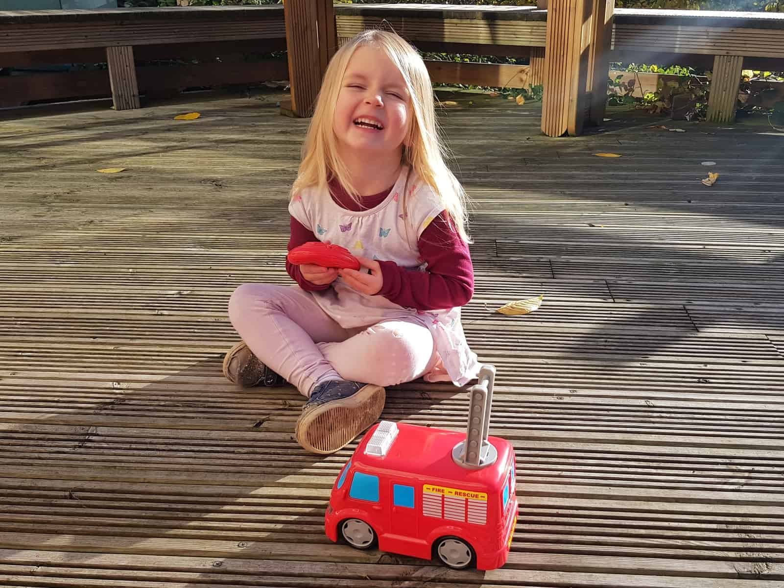 3 year old girl with remote control fire truck