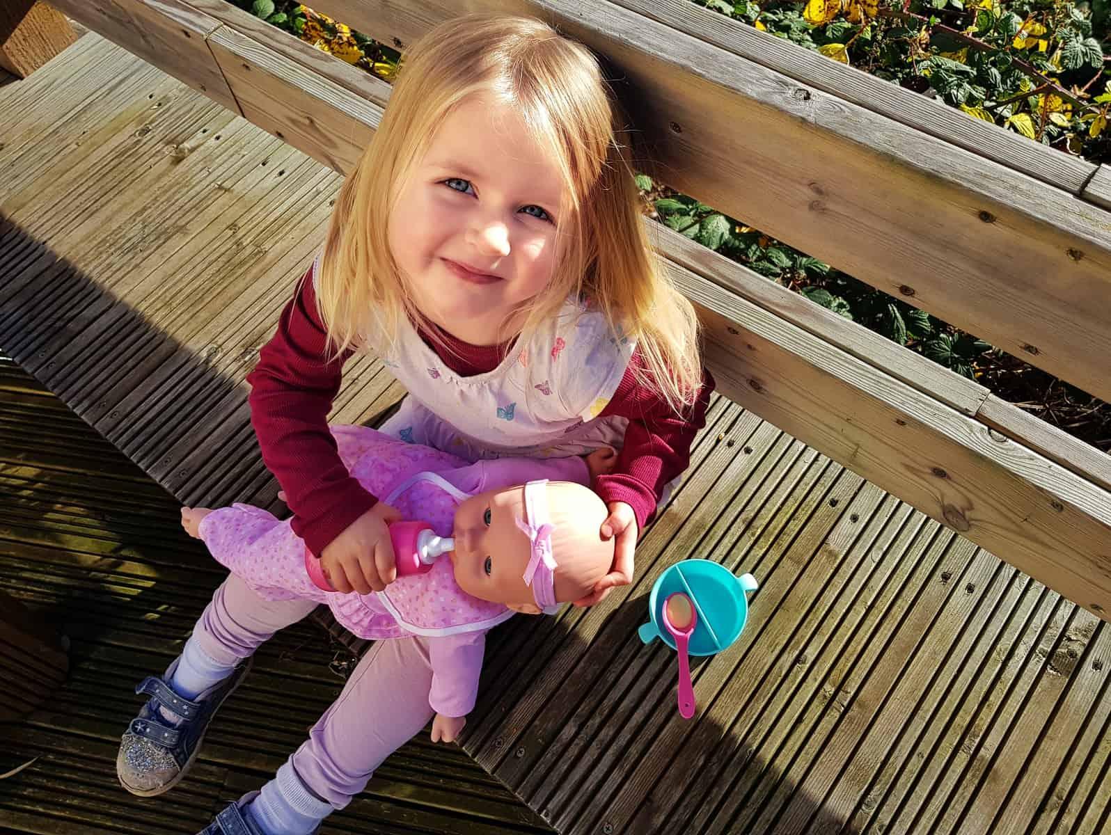 3 year old girl feeding milk to doll