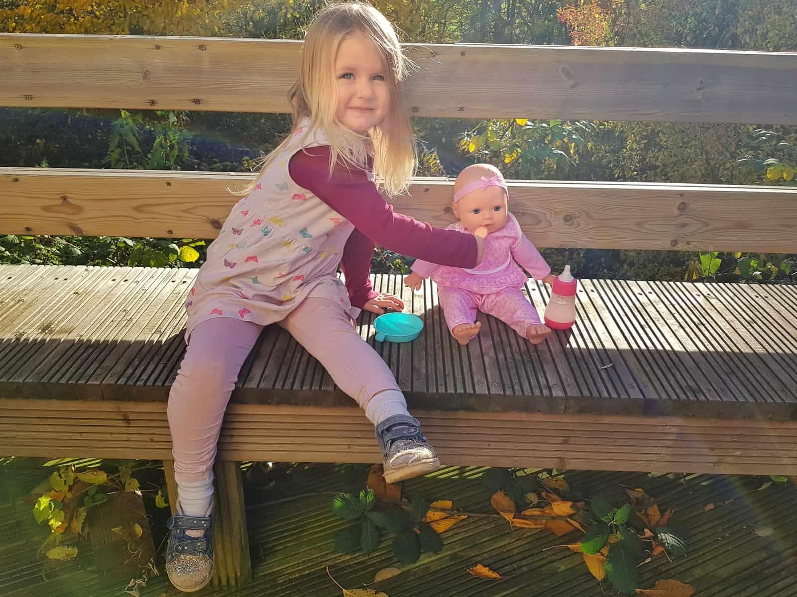 3 year old girl feeding food to doll