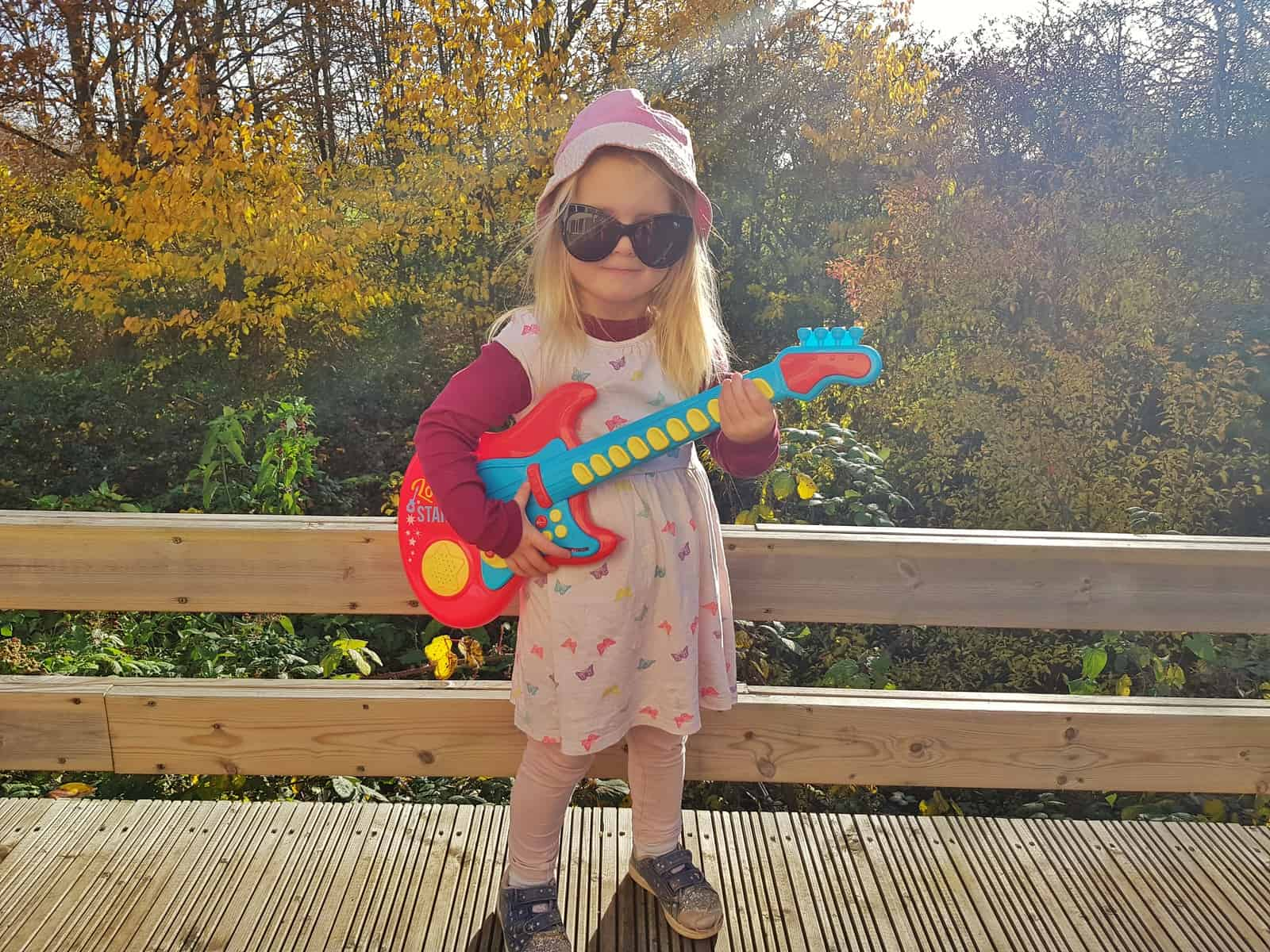 3 year old girl with red and blue plastic guitar