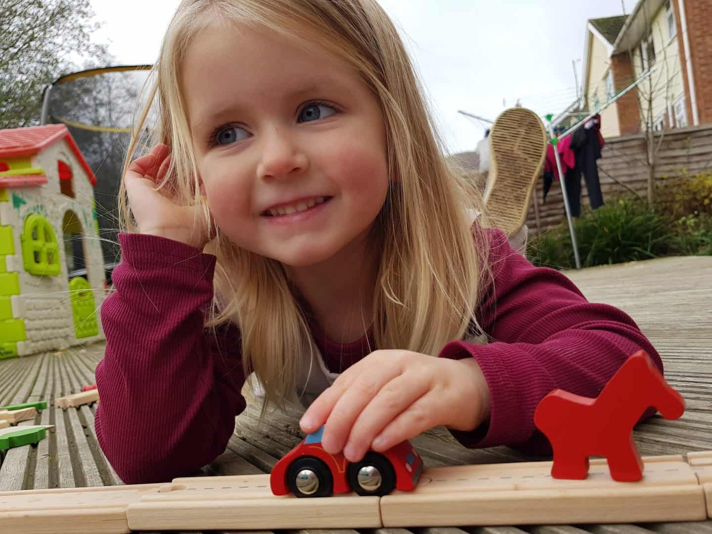 3 year old girl with toy car on a track