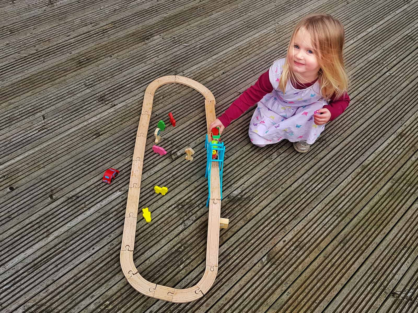 3 year old girl with toy trains on track