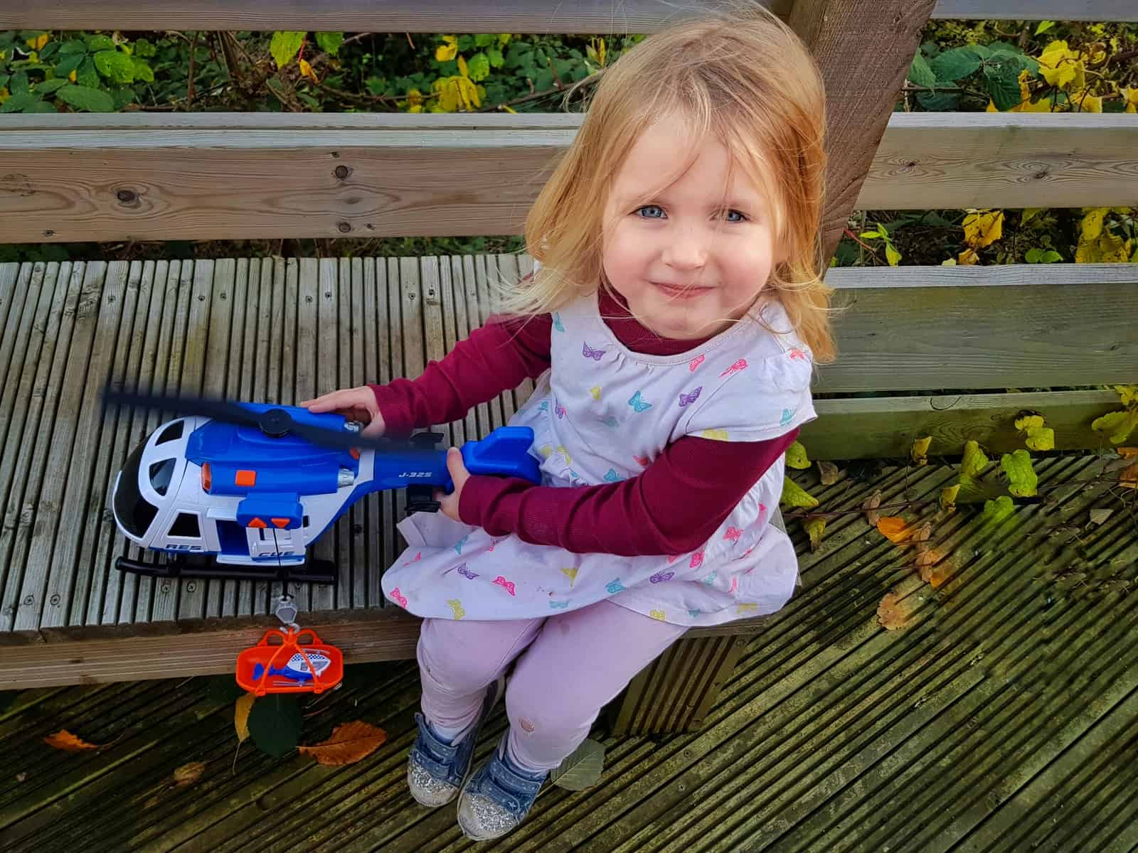 3 year old girl with toy helicopter