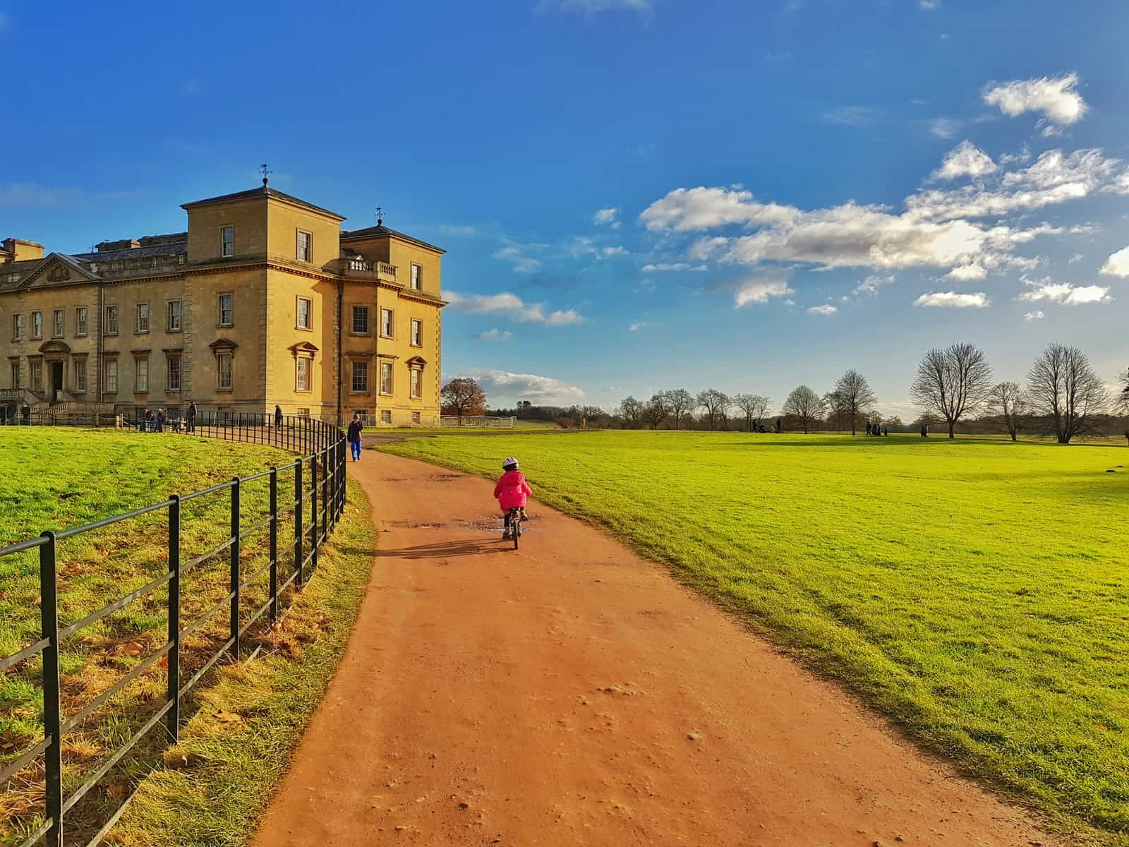 Croome court in the distance with a three year old girl cycling towards it. Blue sky with a few clouds.