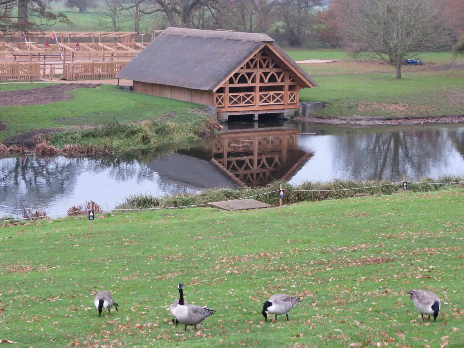 A wooden building with a thatched roof reflected in a river. In the foreground are Canada geese.