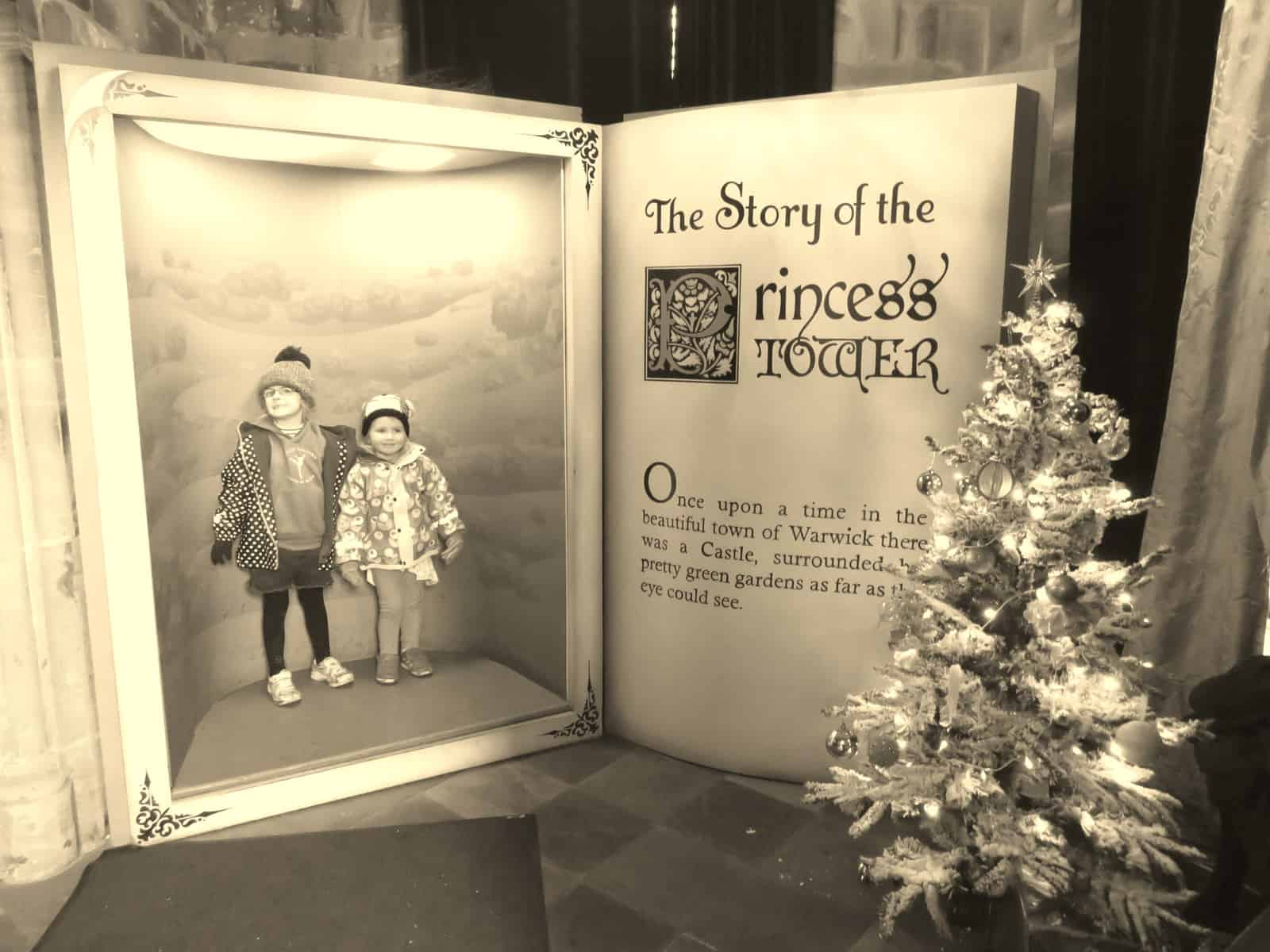 An oversized book - The story of the Princess Tower - the illustration of the book is large enough for two little girls to be standing inside it. A Christmas tree decorated with fairy lights stands in the foreground.