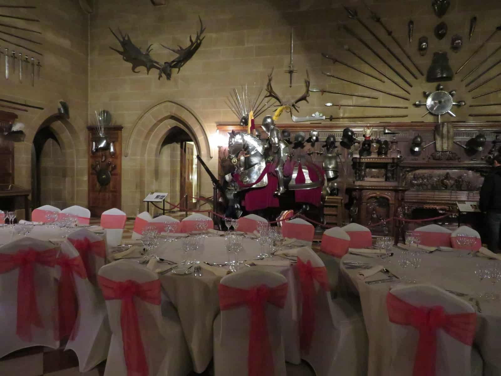 The Great Hall at Warwick Castle with the table set for a wedding with white and pink seat covers and glasses on the table. In the background is a suit of armour of a knight on horseback.