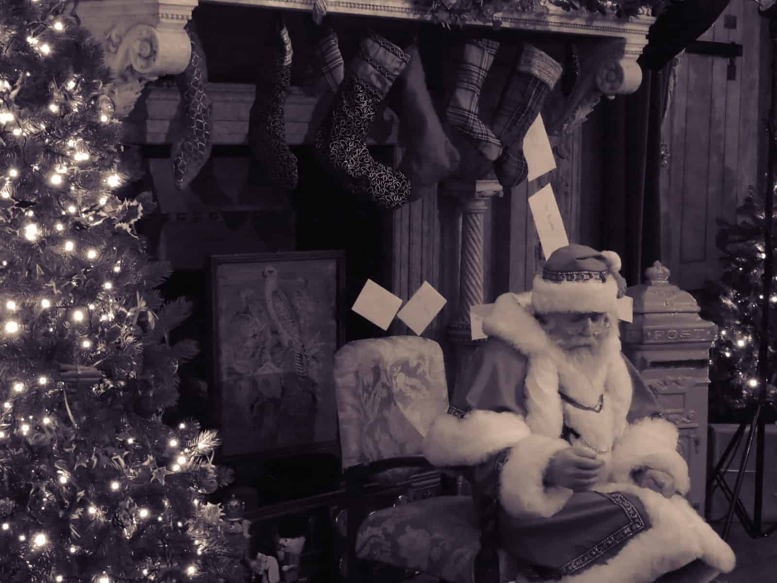 A black and white photo of Santa sat in front of a fireplace with stockings hanging from it with Christmas trees either side.