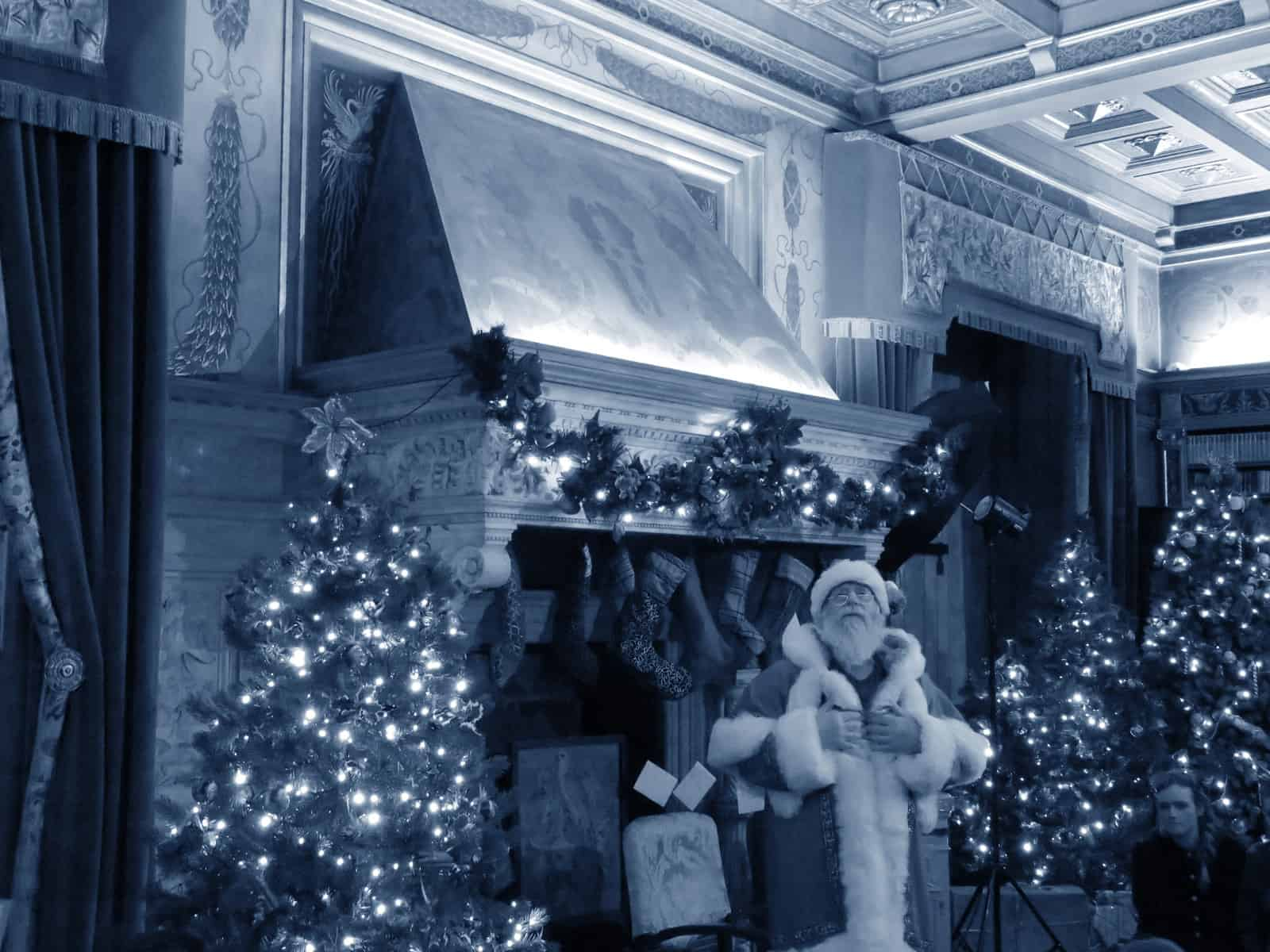 Black and white photo of Santa standing in front of a fireplace looking up. The room is decorated with Christmas trees and stockings and lights are on top of the fireplace.
