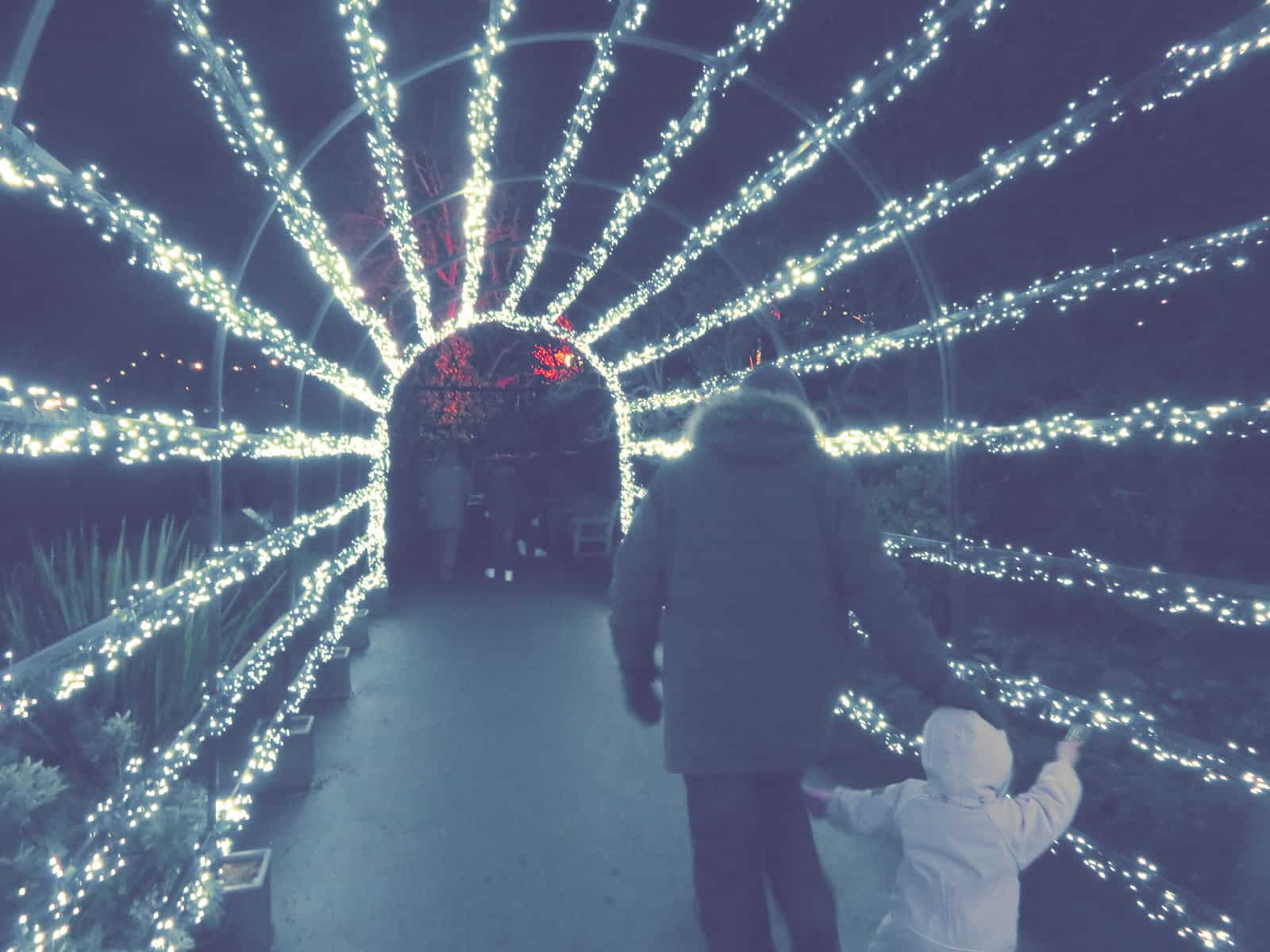 A dad and young daughter walking through an illuminated tunnel