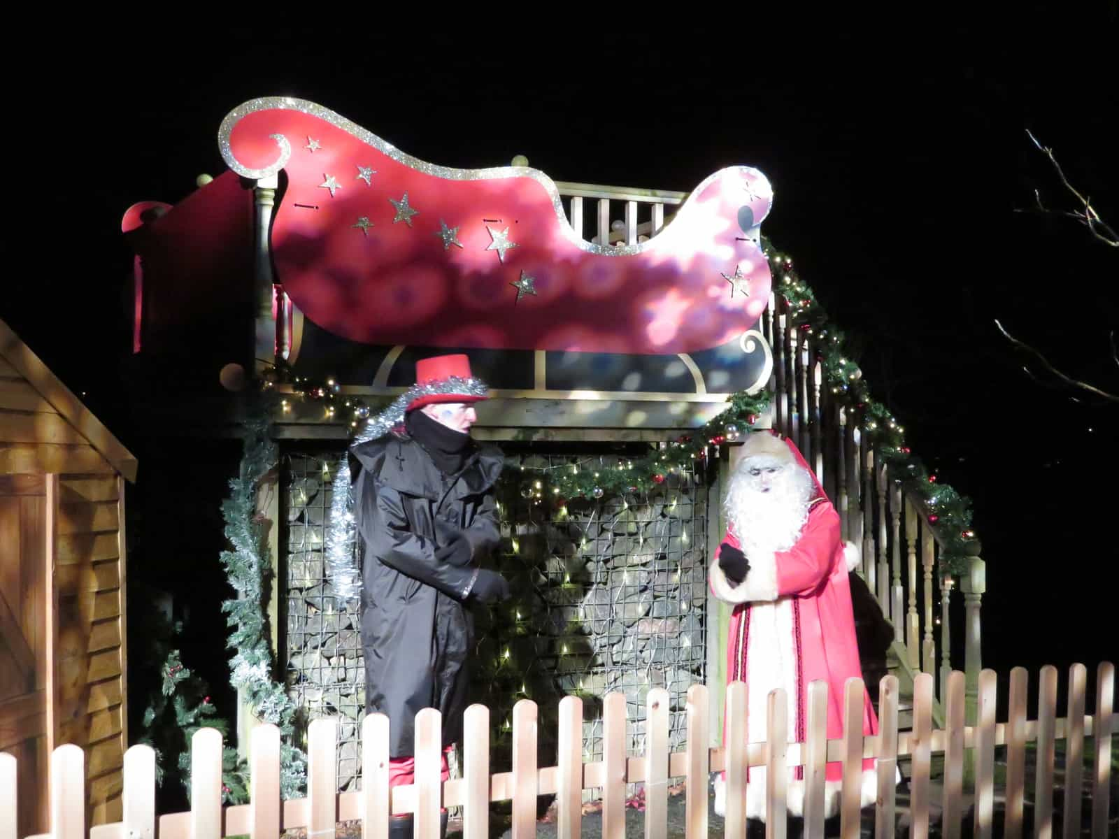 Santa and a helper dressed in black stand beside a sleigh