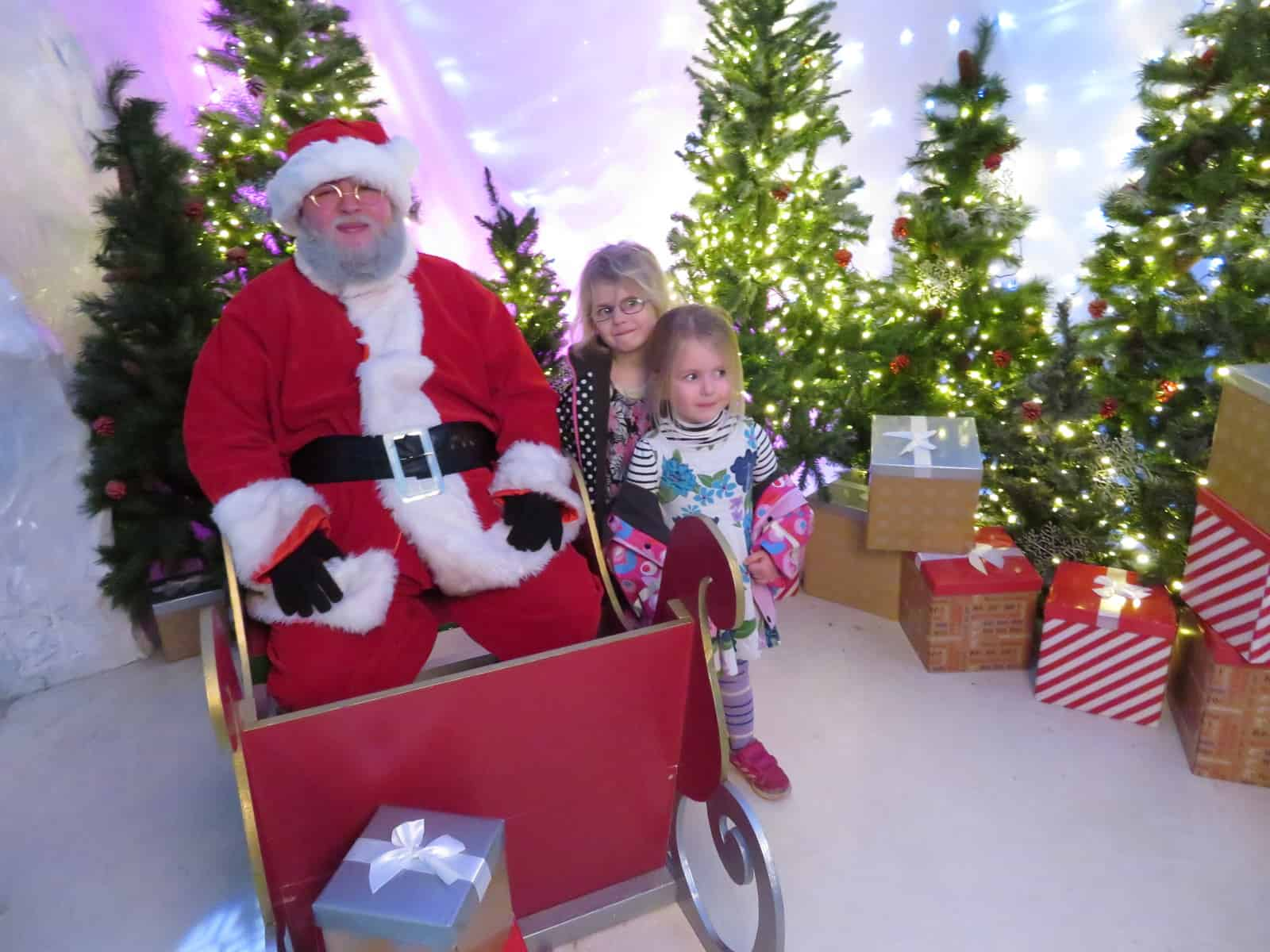 Santa in sleigh with two little girls, Christmas trees in the background