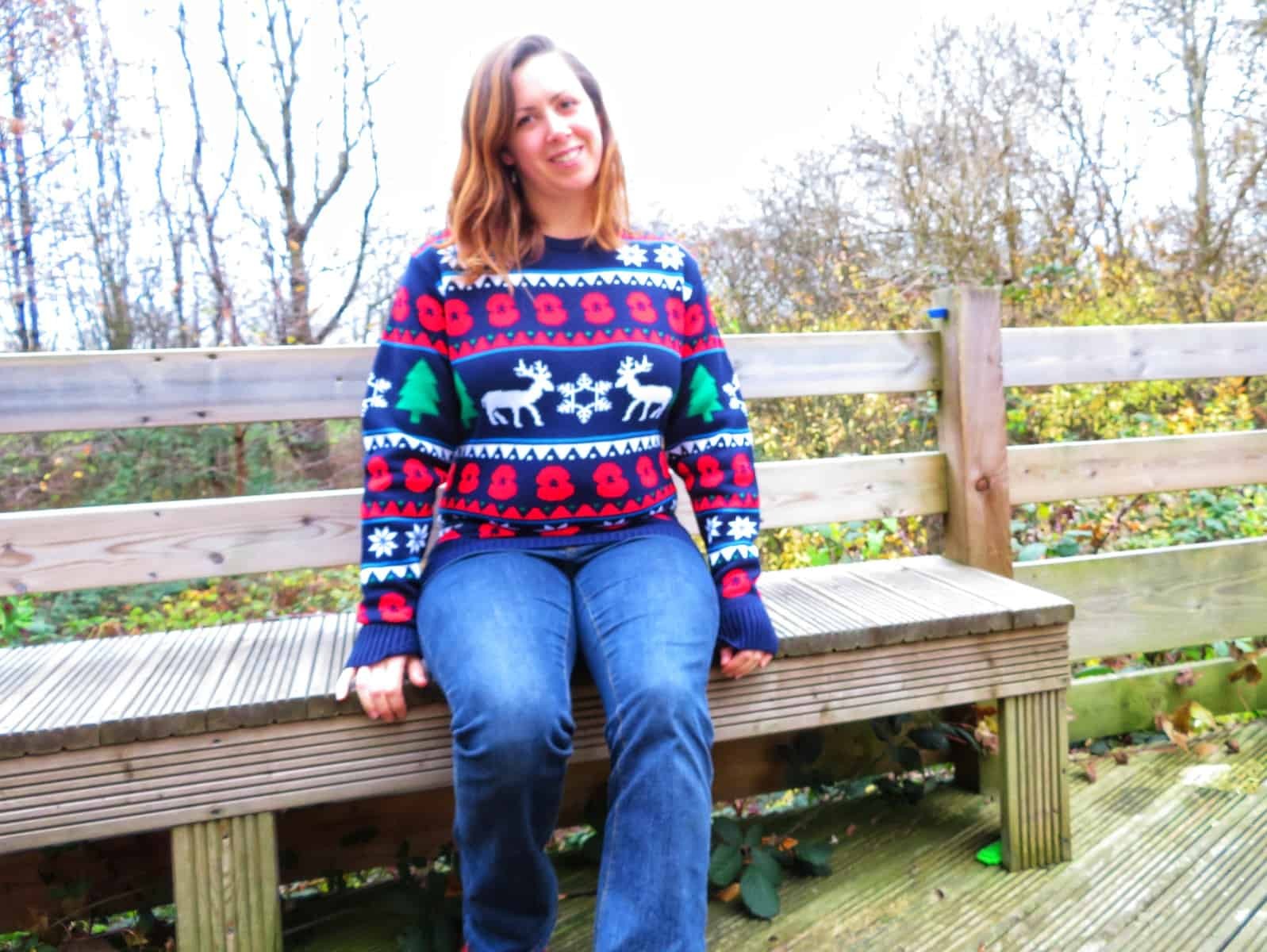 Female sat on a bench outside wearing a Christmas jumper with poppies on