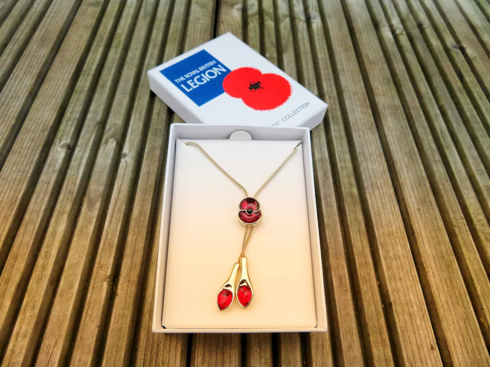 gold necklace with red poppy slider in open white box beside Royal British Legion box lid wit poppy on