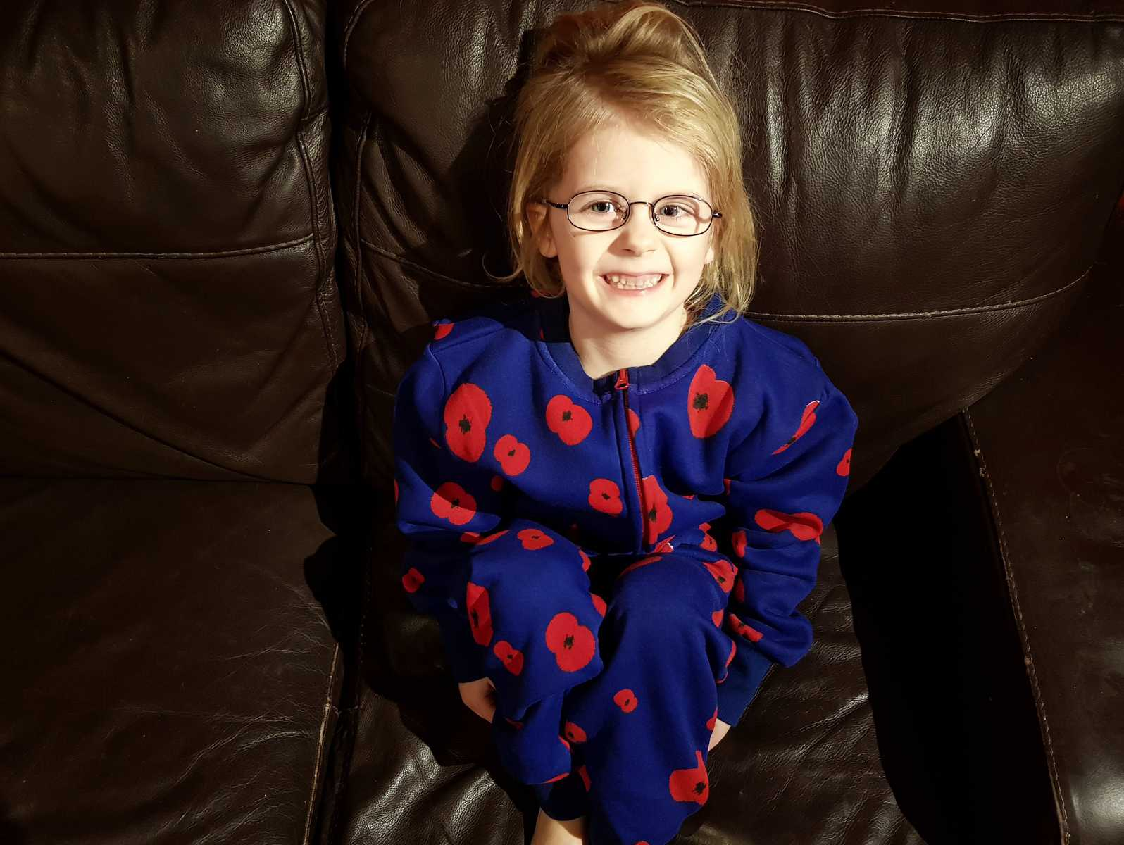 little girl in a blue onesie with red poppies on it