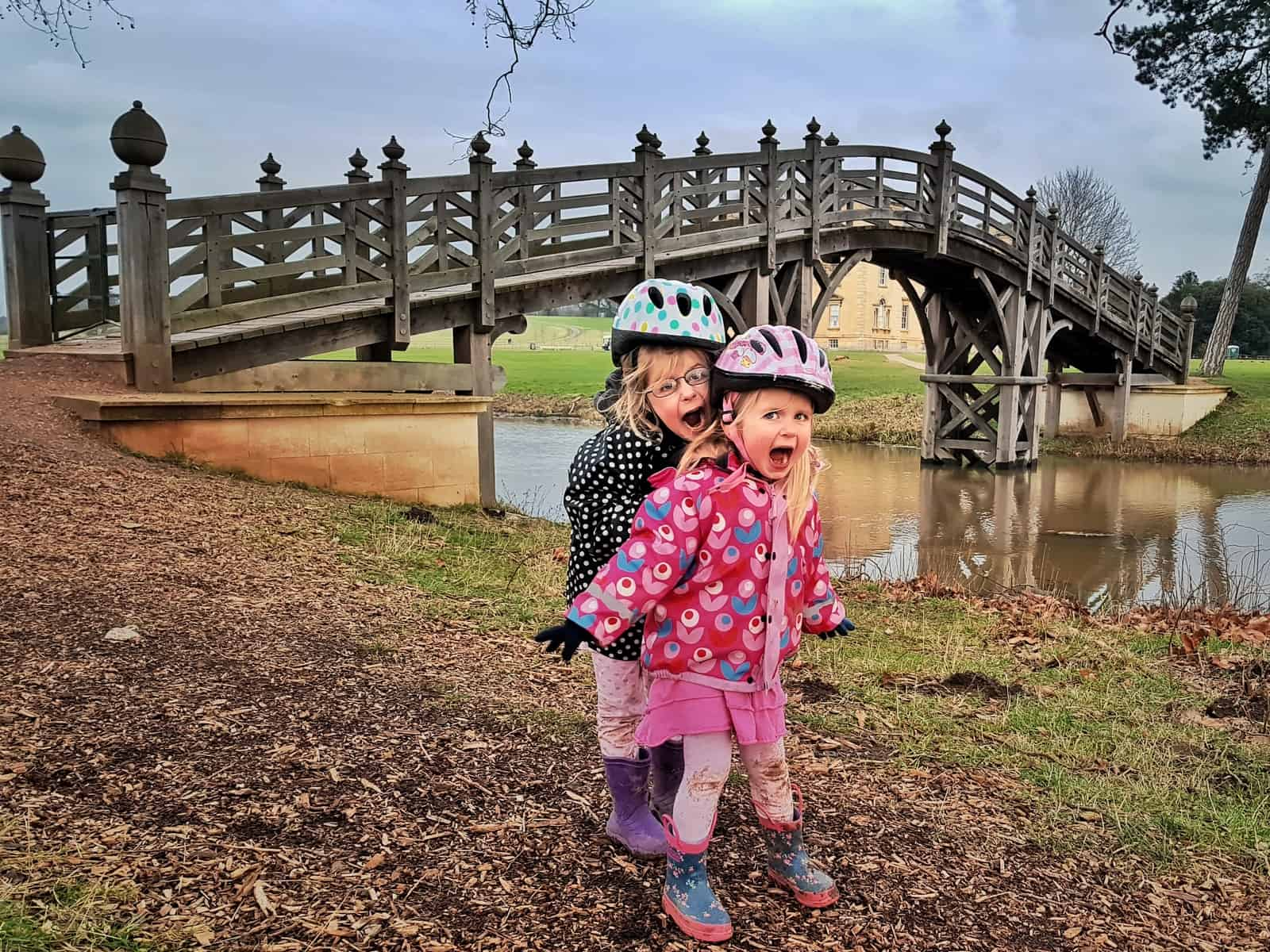 Two young girls standing by a river bridge at National Trust Croome, West Midlands