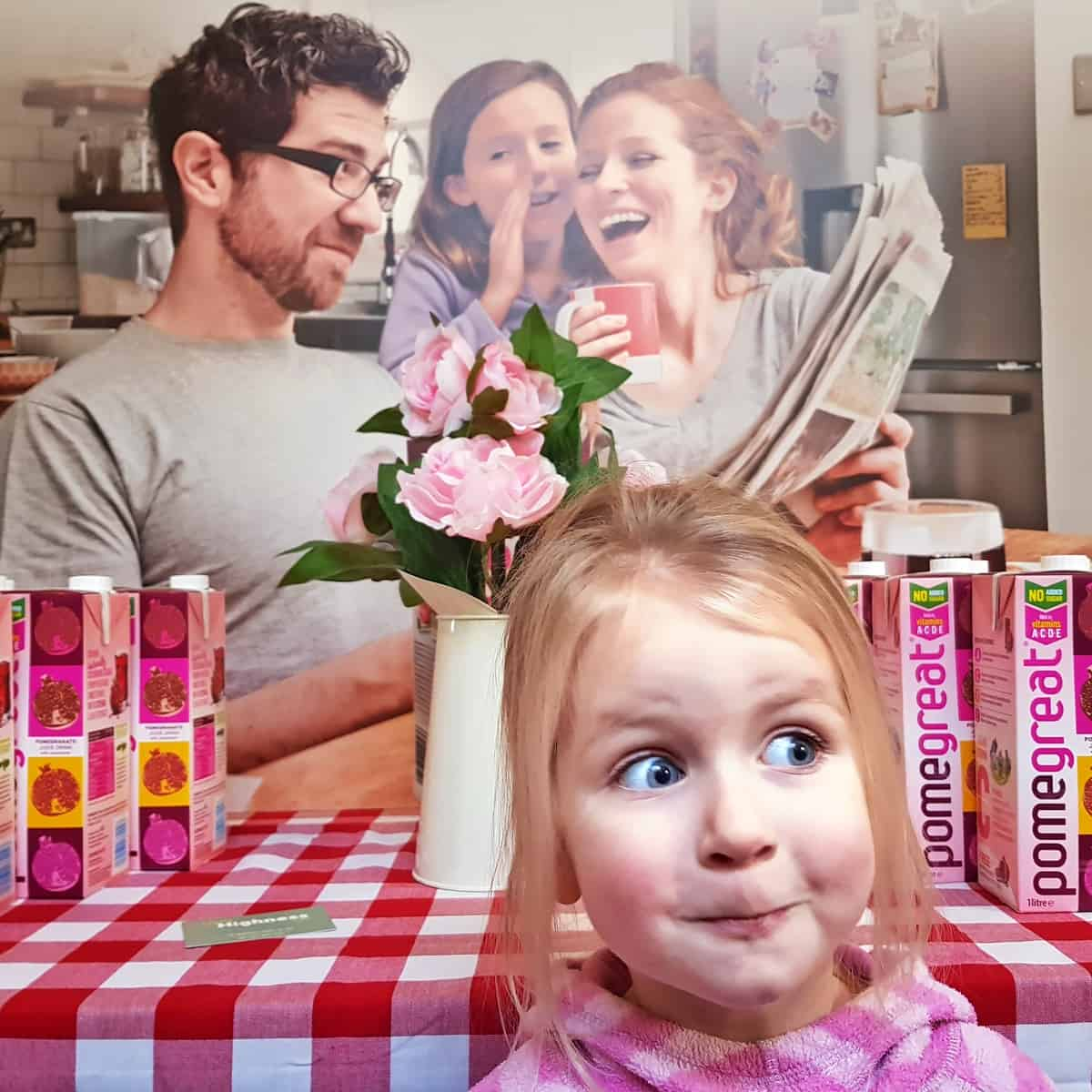 picture of people laughing behind a table with pomegreat on. Little girl pulling a face in front of the table.