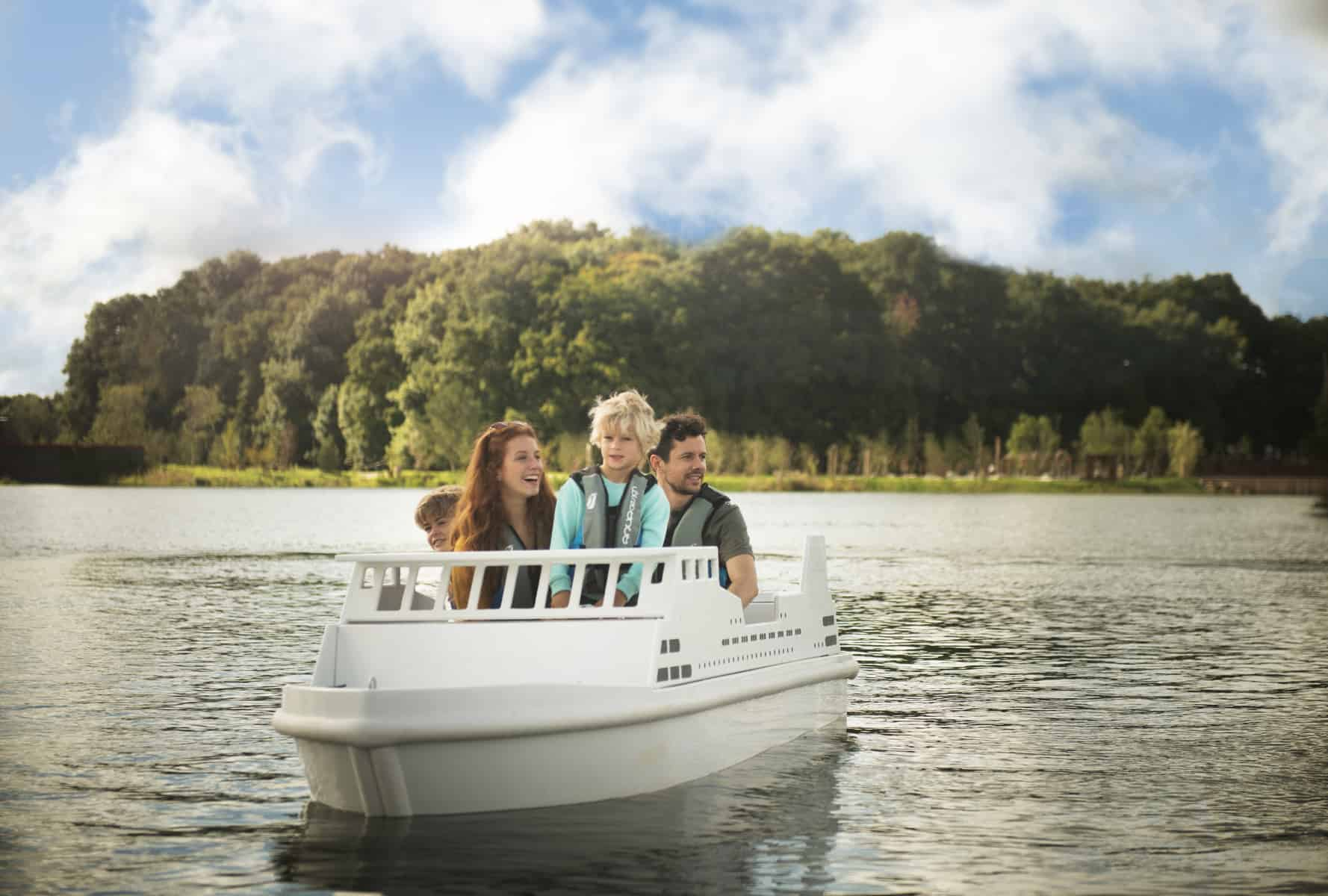 People riding in a small white boat on a lake with trees in the background