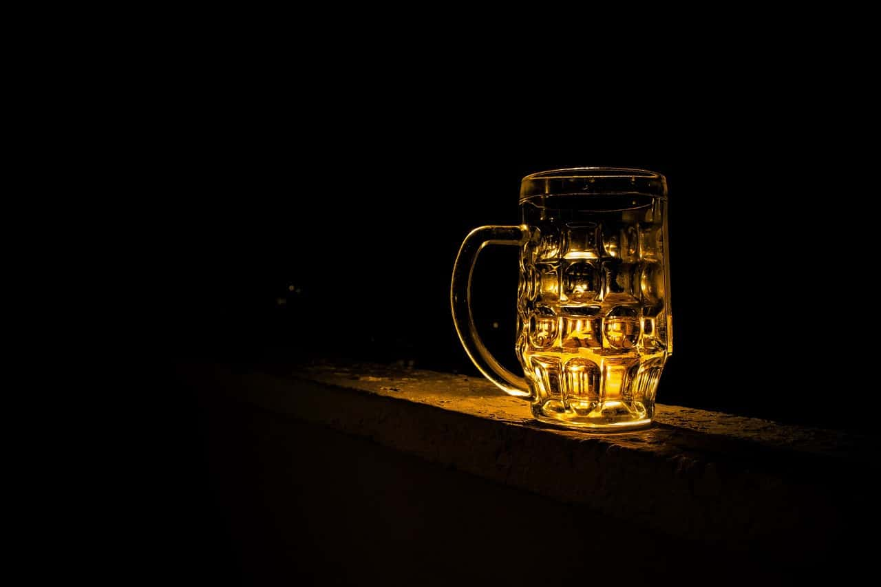 A pint of beer sits on a bar in a dimly lit room