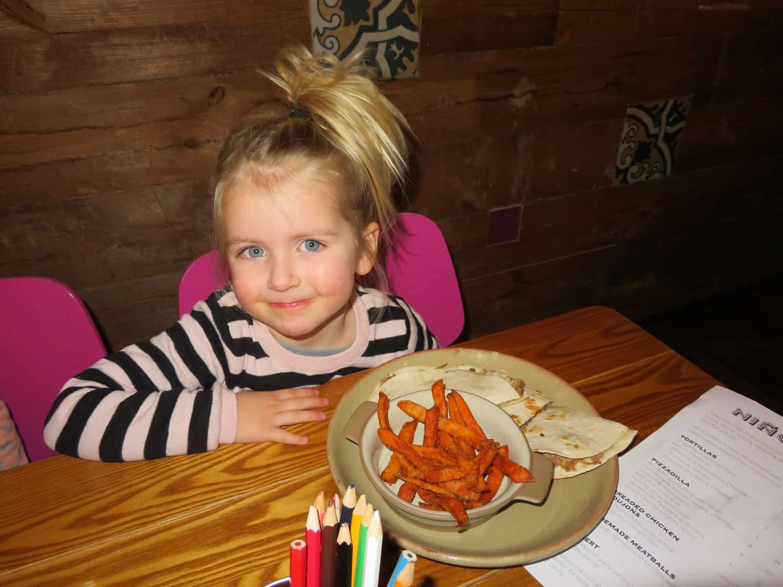 girl sat at a table with plate in front of her containing wraps and sweet potato fries