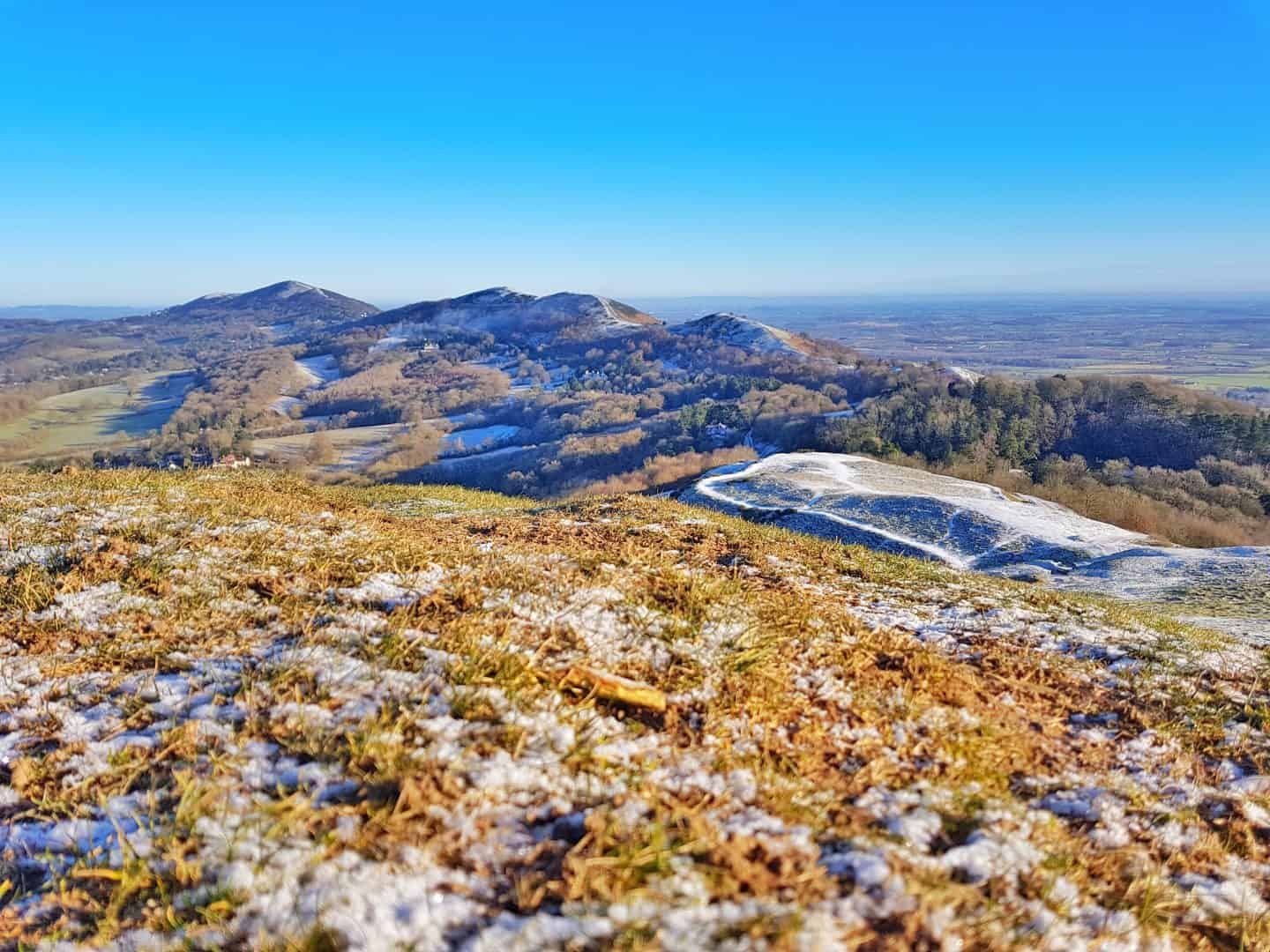 View along the length of the snowy Malvern Hills from the Herefordshire Beacon with blues sky above