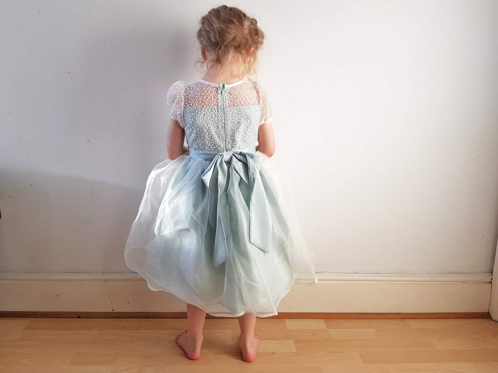 little girl in a mint green flower girl dress with her back to the camera