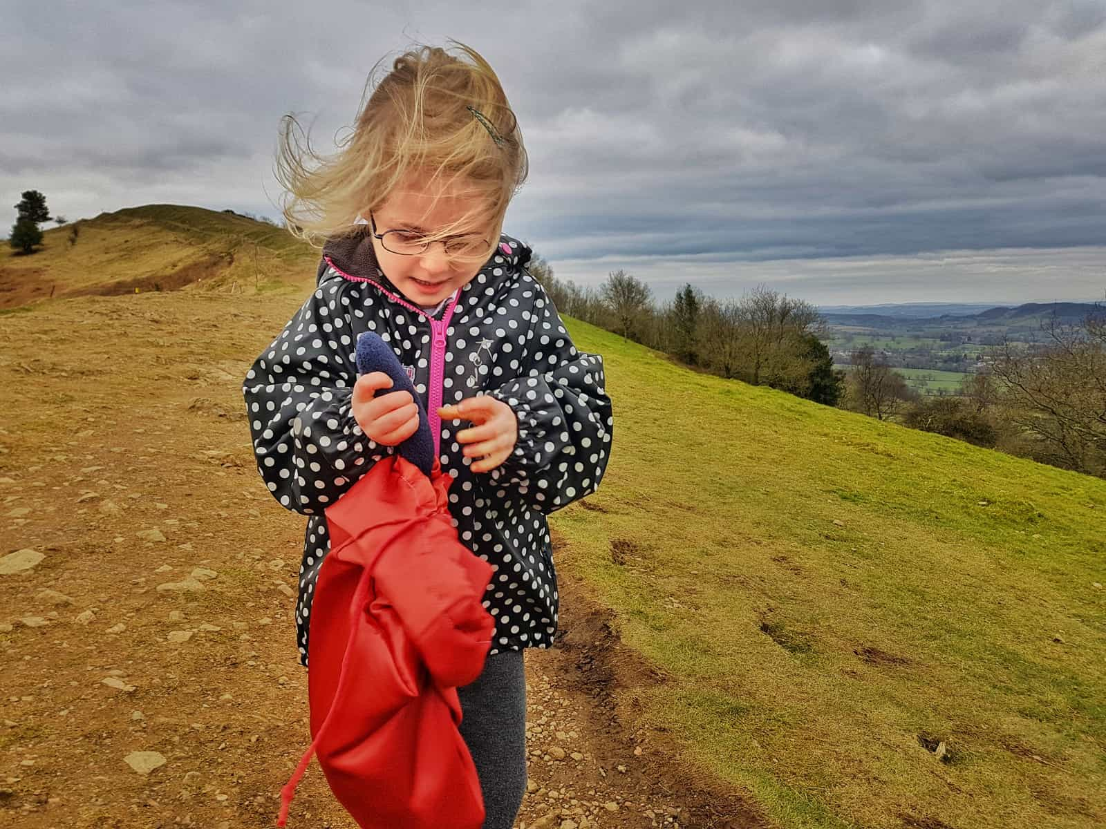 5 year old girl in black and white spotty coat on Malvern hills looking into a red bag