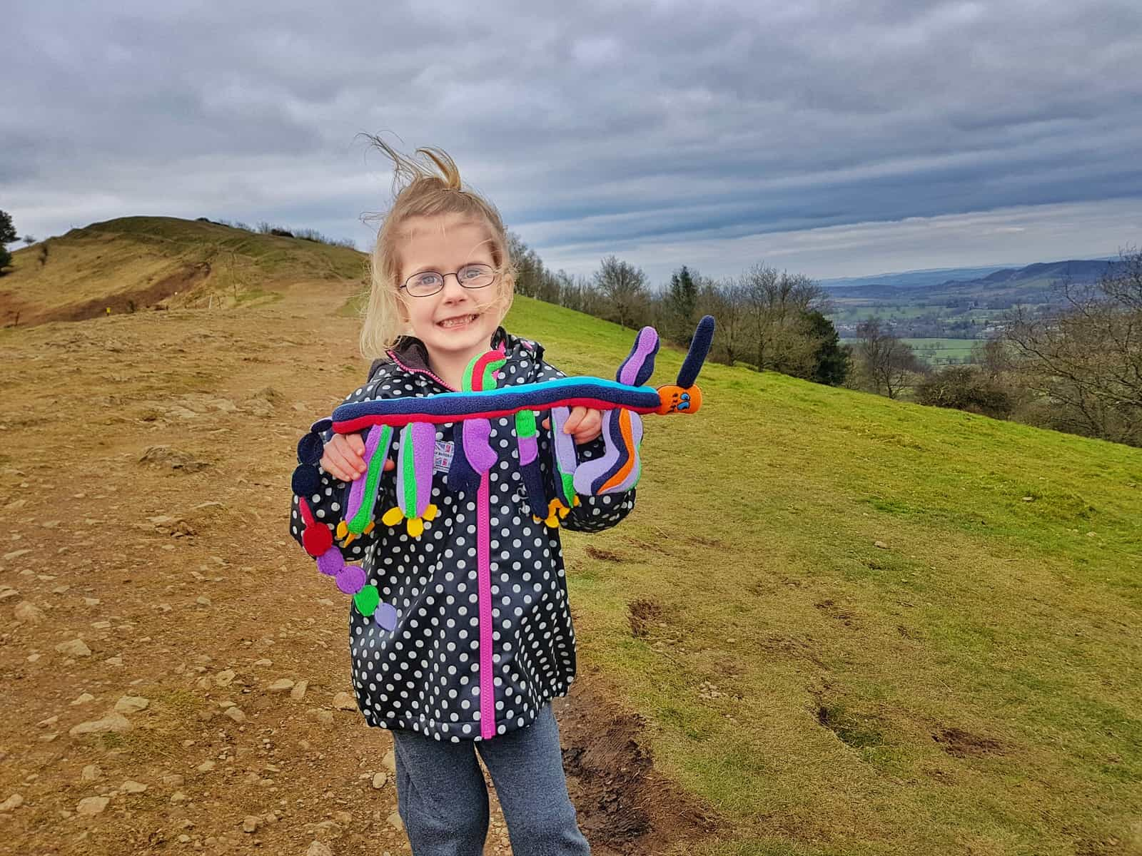 5 year old girl in black and white spotty coat on Malvern hills holding a cuddly toy long in shape with a red face and four legs with a long tail and bits sticking up. Girl is smiling.
