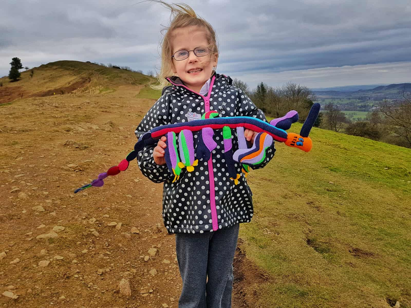 5 year old girl in black and white spotty coat on Malvern hills holding a cuddly toy long in shape with a red face and four legs with a long tail and bits sticking up. Girl looks pleased.