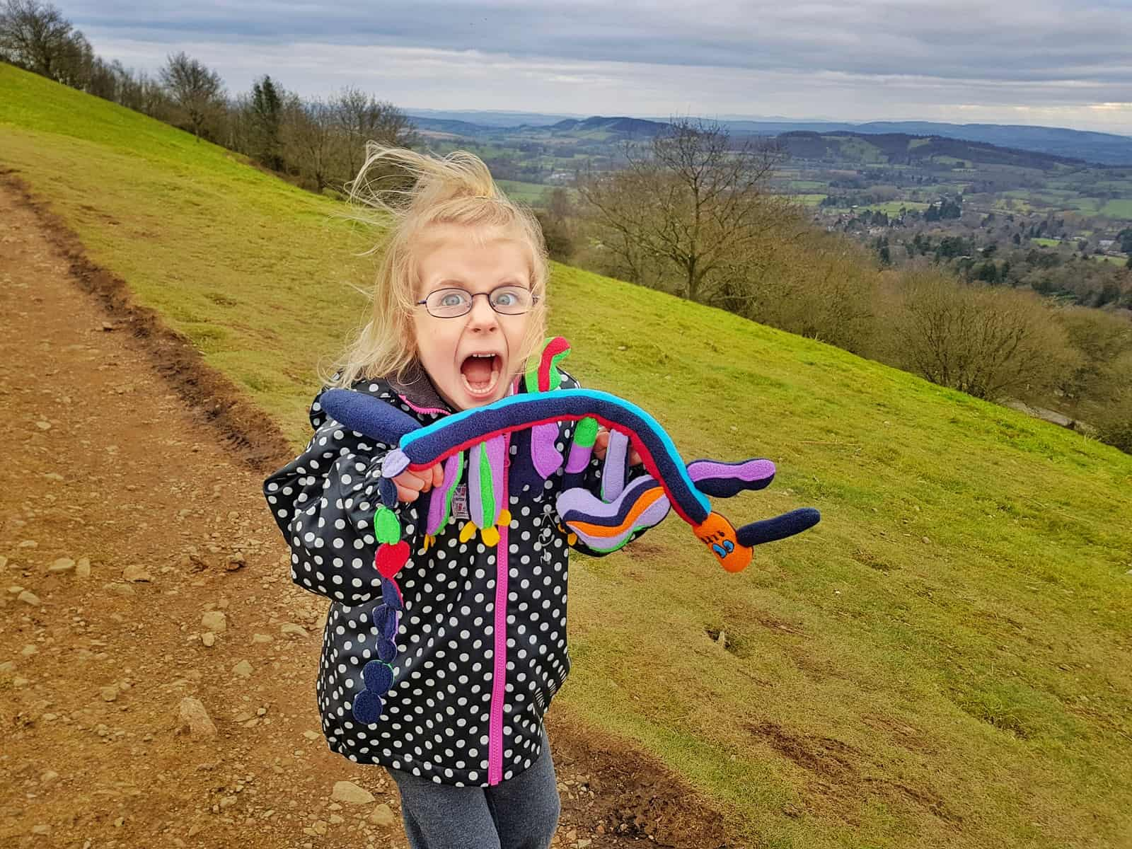 5 year old girl in black and white spotty coat on Malvern hills holding a cuddly toy long in shape with a red face and four legs with a long tail and bits sticking up. Girl is cheering.