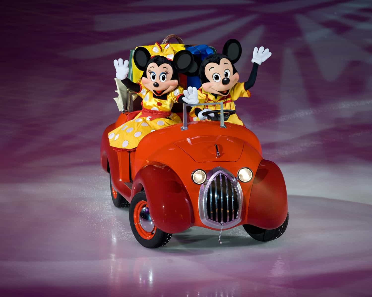 Mickey and Minnie mouse on the ice in a car as part of Disney on Ice Worlds of Enchantment