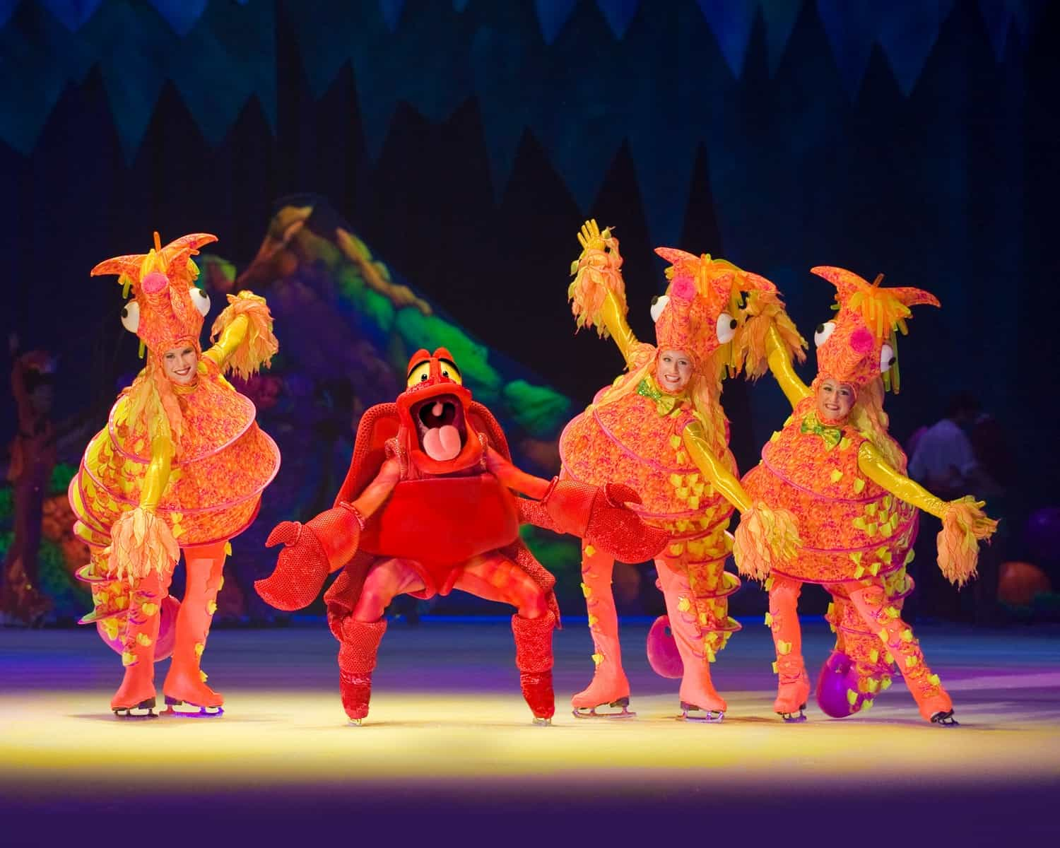 Characters from the little mermaid the crab and some fish on ice skates as part of Disney on Ice Worlds of Enchantment