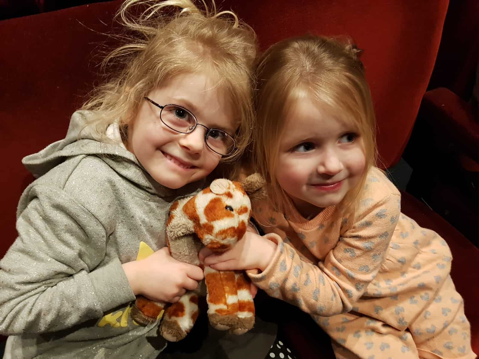 Two little girls and a toy giraffe waiting to watch The Jungle Book at Malvern Theatres.