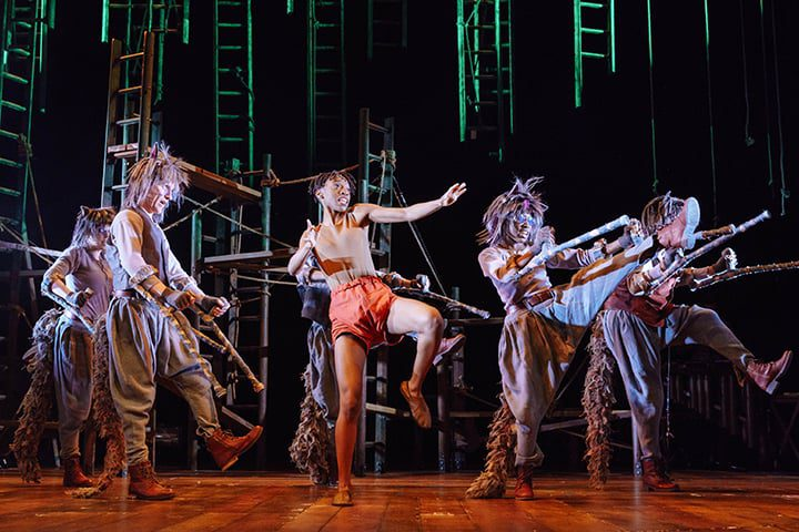 Mowgli dancing on stage with the wolf pack in The Jungle Book at Malvern Theatres.