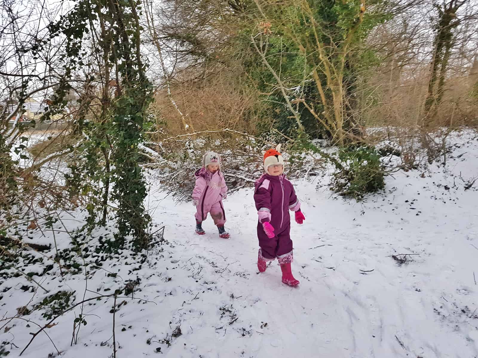 Two young girls walking along outside in the snow