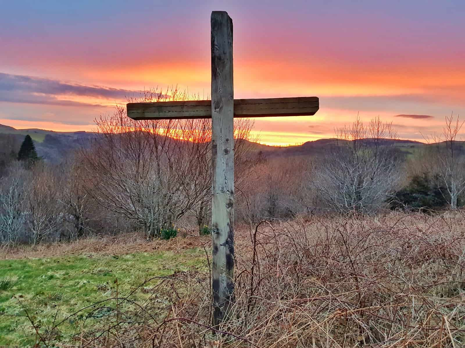 Cross in foreground with sun setting over hills behind taken at a campsite in Devil's Bridge, a stop on the Vale of Rheidol Railway