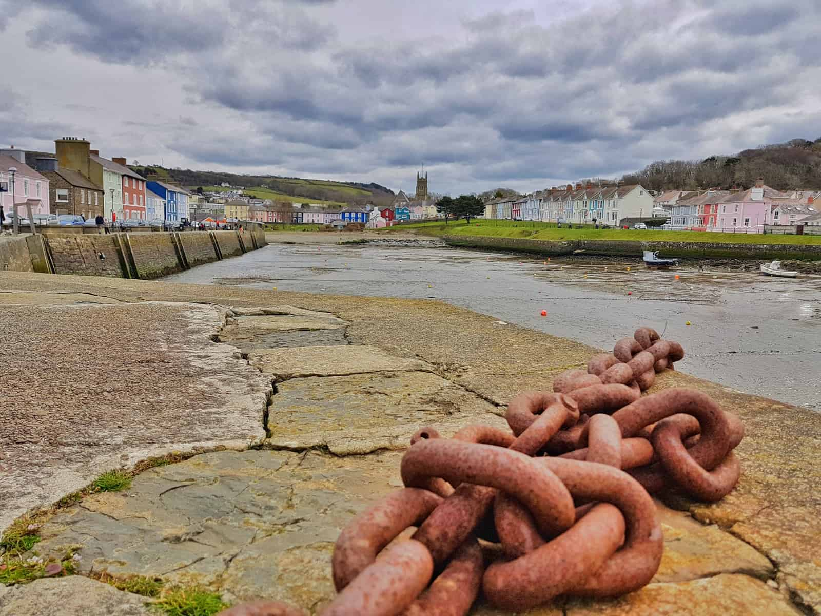 View across Aberaeron harbour at low tide with colourful houses in background and anchor chain in foreground